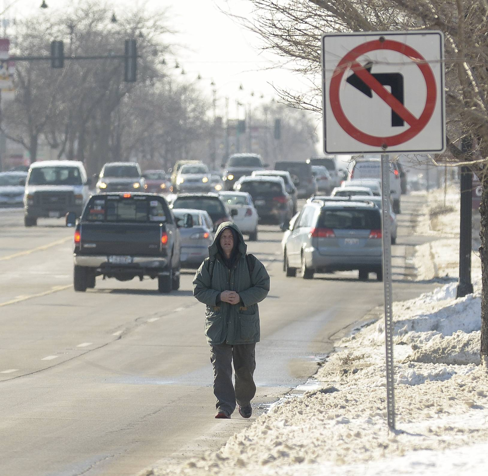 "It's difficult for Patrick Bettis of Glen Ellyn to walk on the snowy sidewalk along Roosevelt Road in Glen Ellyn, so he regularly walks in the street during his twice-weekly trip to physical therapy. ""If you don't want to get hit, you got to get wet,"" he said."