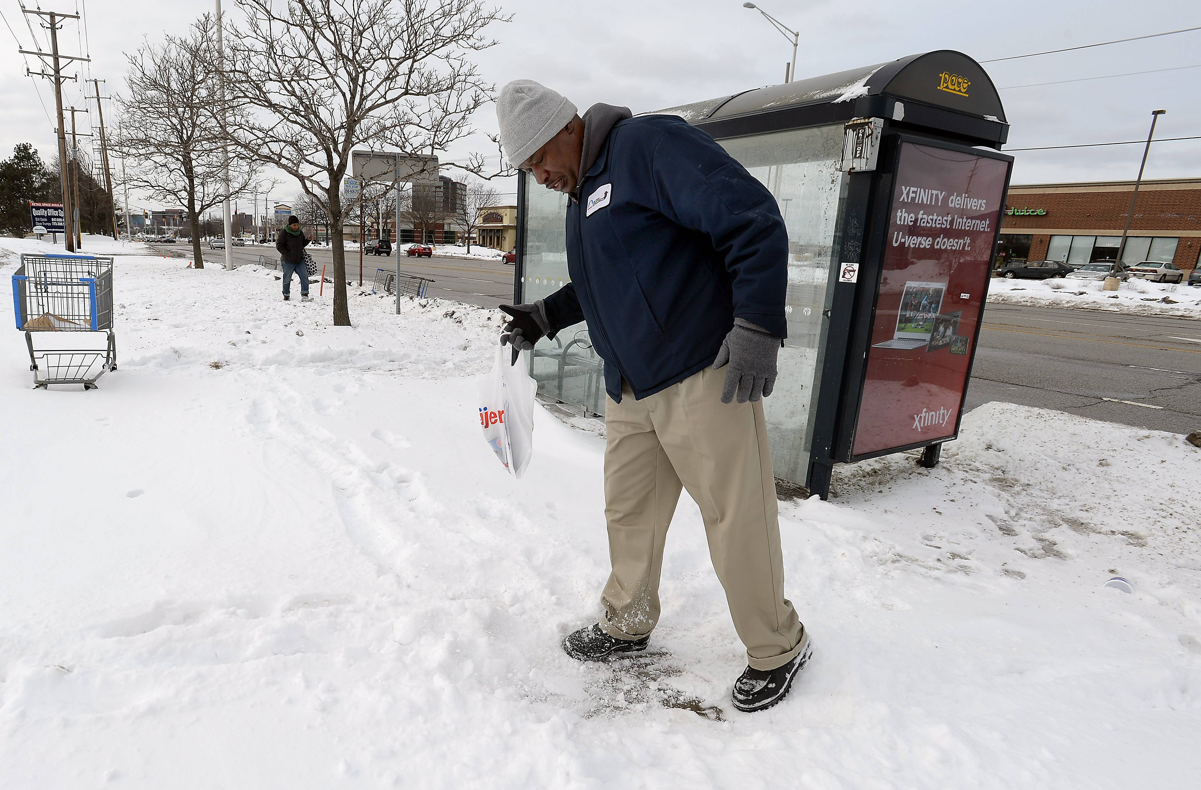 "Charles Robinson of Mount Prospect clears snow from a section of the sidewalk at the Pace bus stop along Golf Road in Rolling Meadows. ""It's crazy. What is a person supposed to do?"" he said of the snowy sidewalk. ""We can't walk in the street ... you take a real chance of losing your life."""