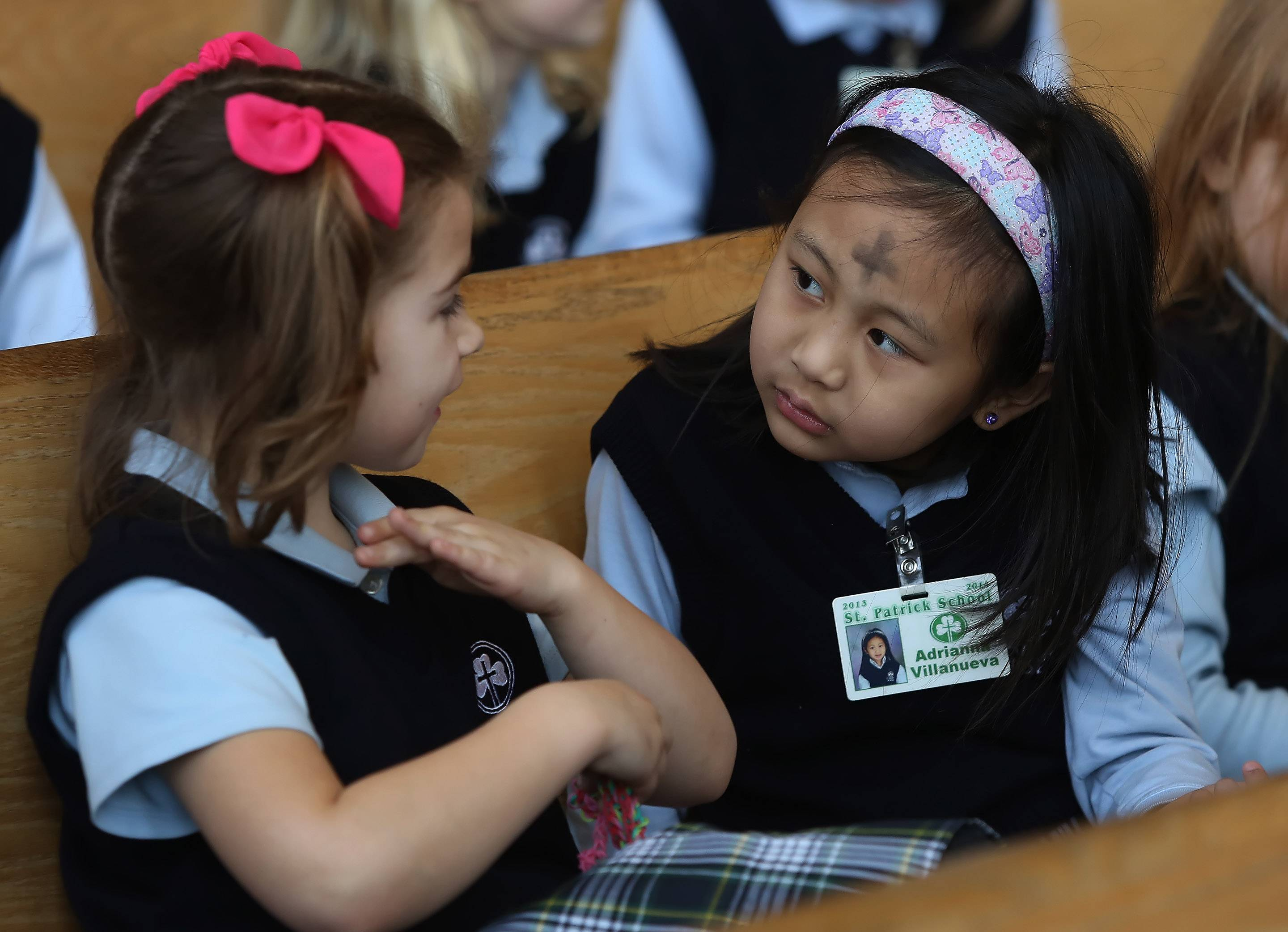 St. Patrick School first graders Brianna Brincks, left, and Adrianna Villanueva, talk about thier ashes on their foreheads as they attended Ash Wednesday service at St. Patrick Catholic Church in Wadsworth. Ash Wednesday marks the beginning of Lent that culminates in Easter Sunday.