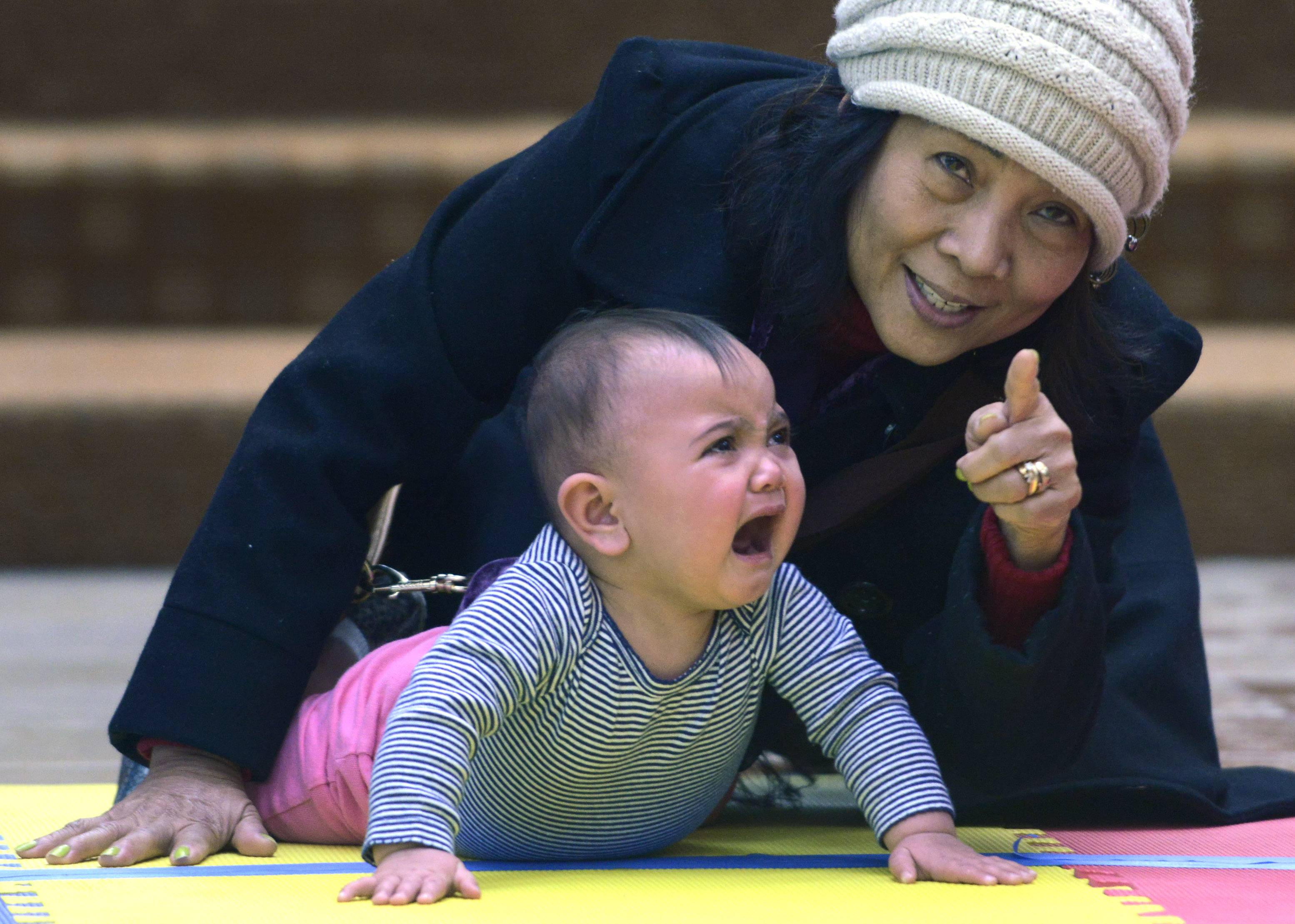 "Jacqueline Ferrer, age 10-1/2 months, of Schaumburg, cries despite the encouragement of her grandmother, Nelly Ferrer, of Des Plaines, during the ""Diaper Derby"" at Woodfield Mall in Schaumburg Saturday. Jacqueline went on to win the heat."