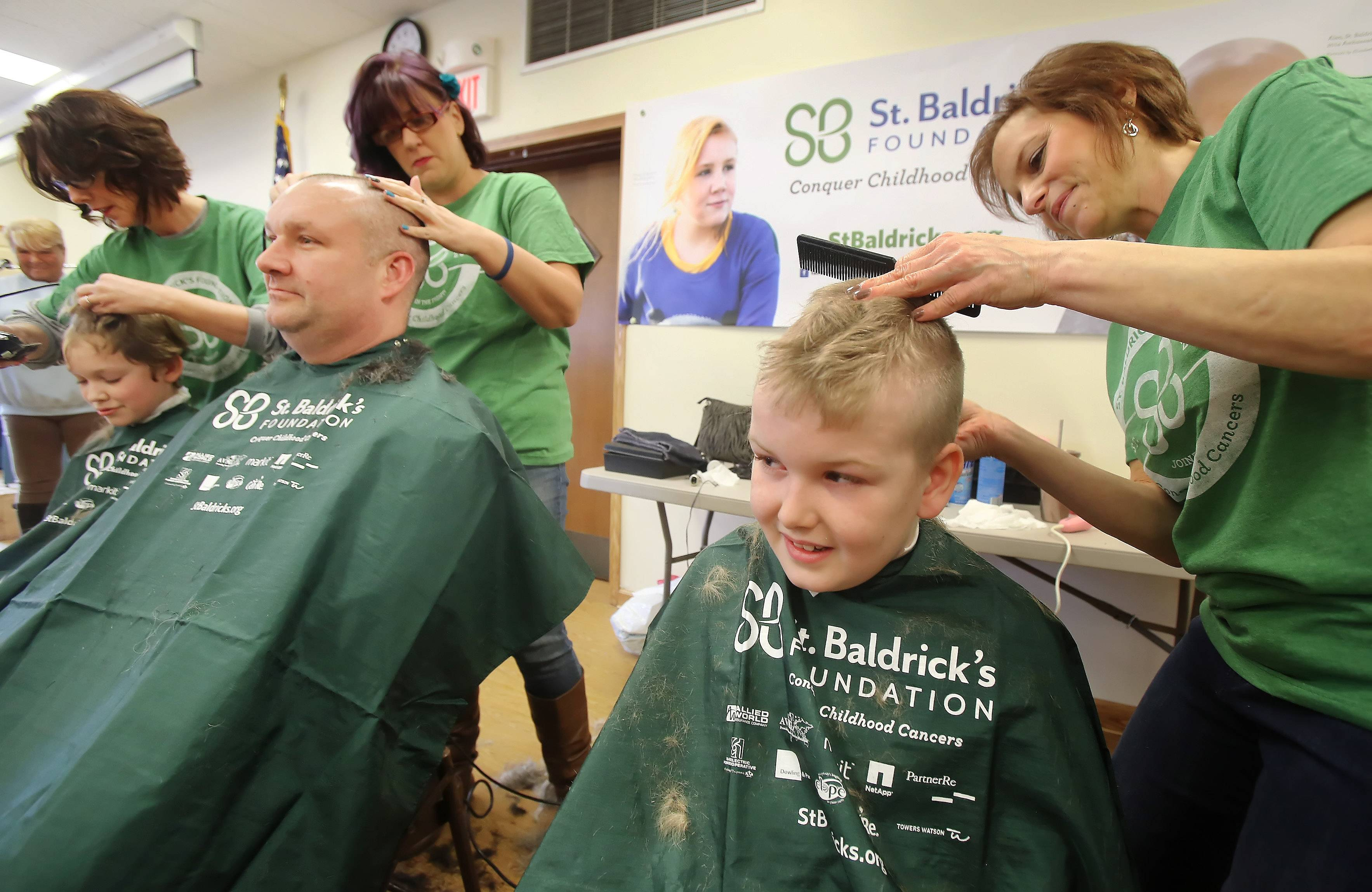 "Conner Torkillsen, 8, of Lake Villa, has his hair cut by Trish Griffin of Shear Genius, while his dad, Dave, and brother, Matthew, get theirs sheared nearby during the ""Taking It All Off for Cancer"" event Sunday at the Fox Lake Fire Department Bingo Hall. Firefighters, police, and the general public had their heads shaved to raise money for cancer research through the St. Baldrick's Foundation."