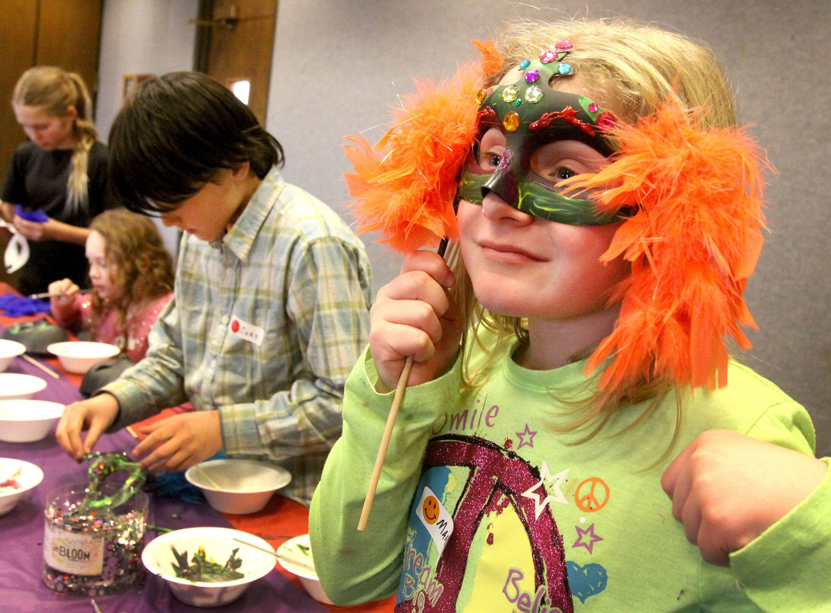 "Mary Holm, 9, shows off her Mardi Gras mask as Croy Knecht, 11, left, paints his mask during Kids Carnivale on Fat Tuesday at the Villa Park Public Library. Kids used paint, sequins, feathers and beads to decorate their masks. ""We're trying to incorporate more art into the library,"" said freelance artist Wendee Goles, of Villa Park, who offered the workshop. She also plans to do an art workshop at the library on Earth Day using recylcled products."