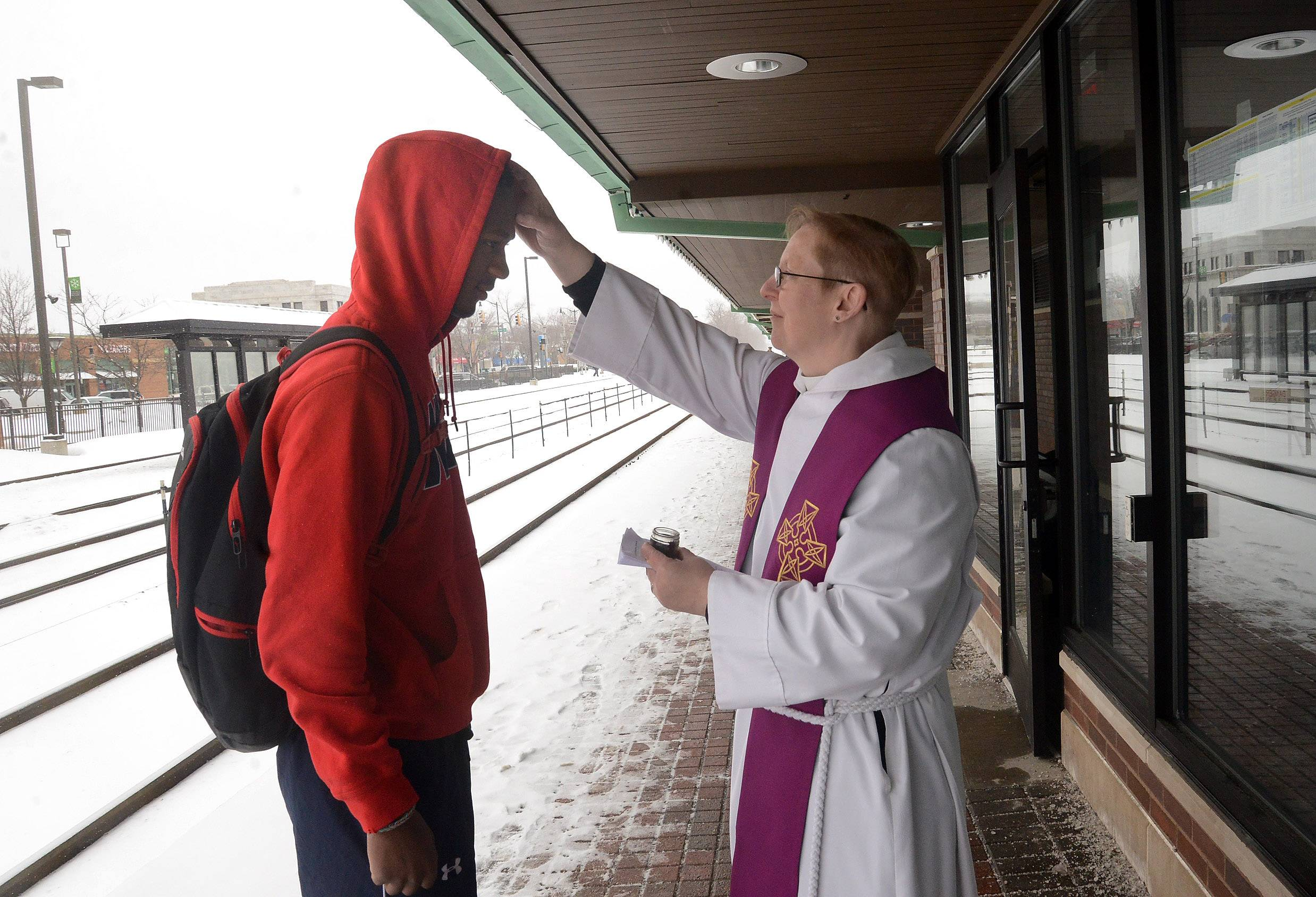"Rev. M.E. Eccles, of St. Martin's Episcopal Church in Des Plaines, provides ""ashes to go"" Wednesday to Ola Arogundade, of Wheeling, at the Des Plaines Metra train station."