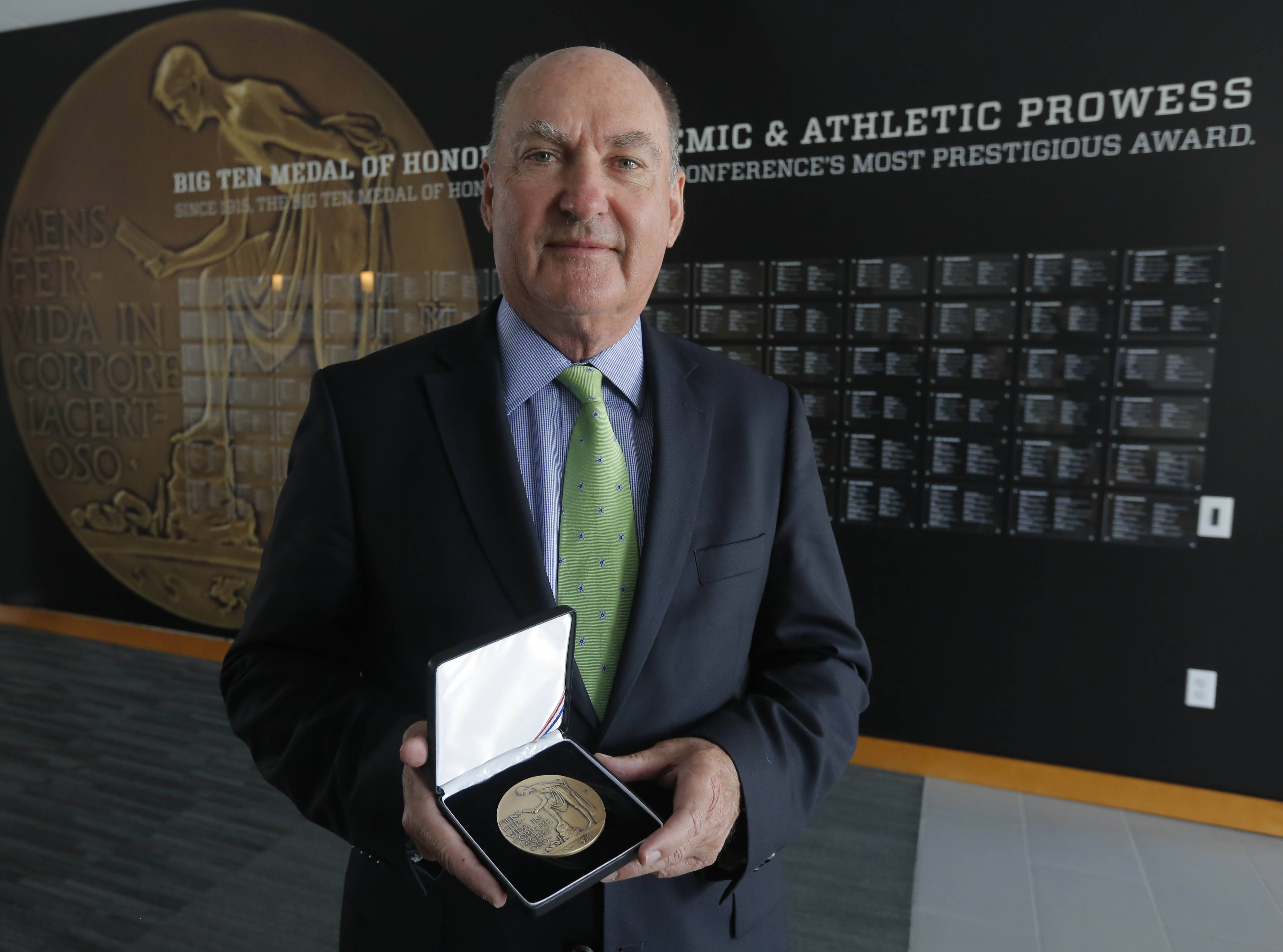 Big Ten commissioner Jim Delany holding the Big Ten Medal of Honor that is exhibited in the The Big Ten Experience at the Big Ten conference's sparkling new headquarters in Rosemont. This year marks the 100th anniversary of the Big Ten Medal of Honor given to one male and female from each school based on their accomplishments on the field and in the classroom, and they are recognized here.