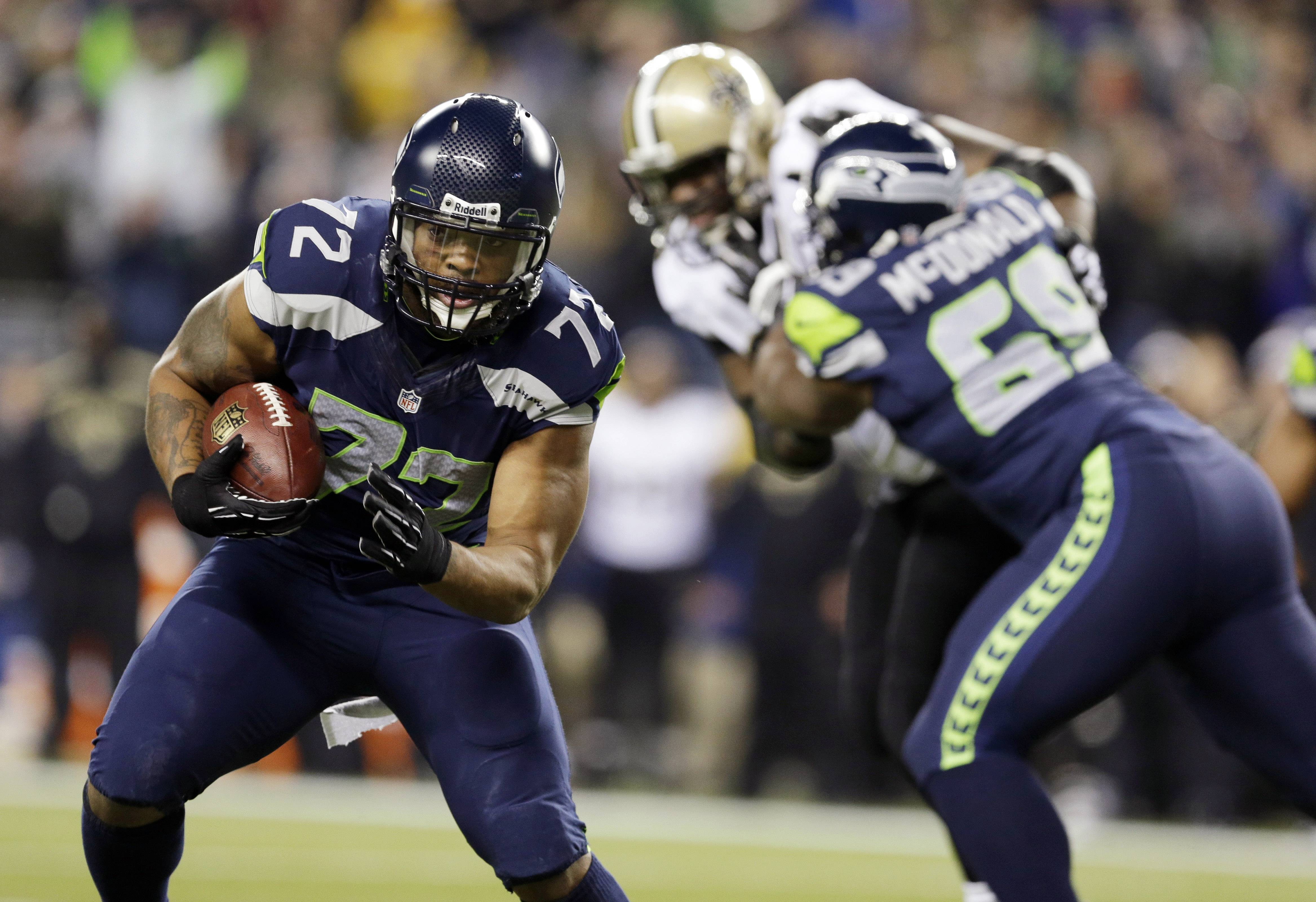 Seattle defensive end Michael Bennett returns a fumble for a touchdown during a game against the Saints last season. The Seahawks announced Monday that Bennett had signed a multiyear deal with the team.