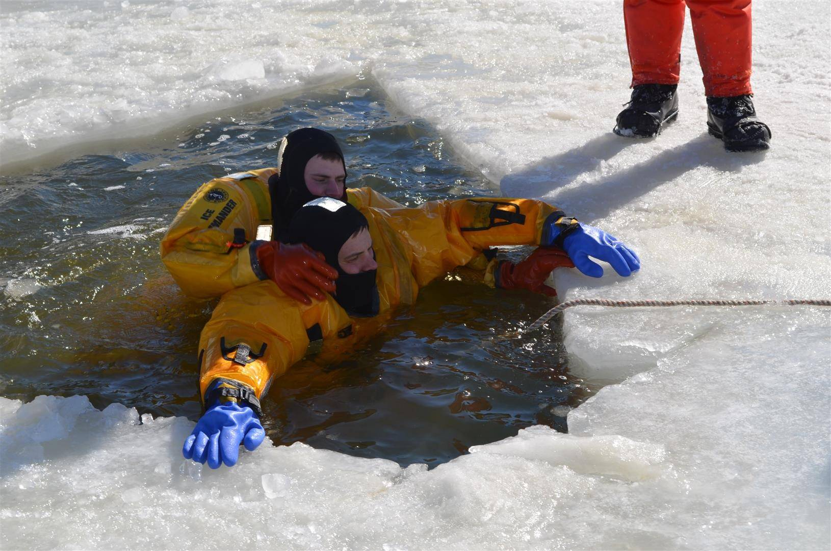 Fire personnel from multiple departments practice ice rescues under hazardous conditions.