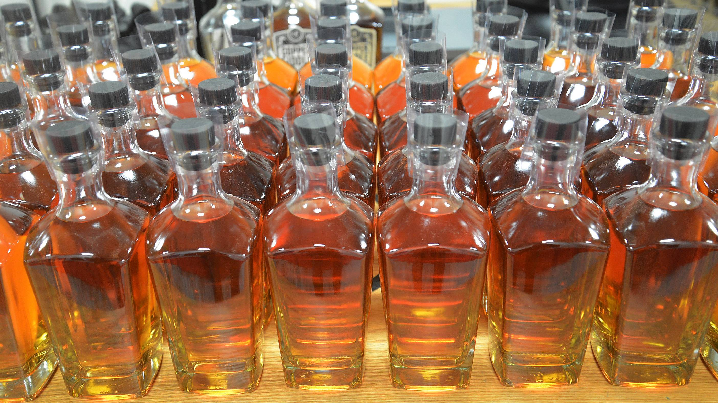 Fred Robinson and Jose Hernandez of Copper Fiddle Distillery in Lake Zurich produce small-batch bourbon and gin in their artisan business. This shrink-wrapped bottle of bourbon is ready to be labeled.