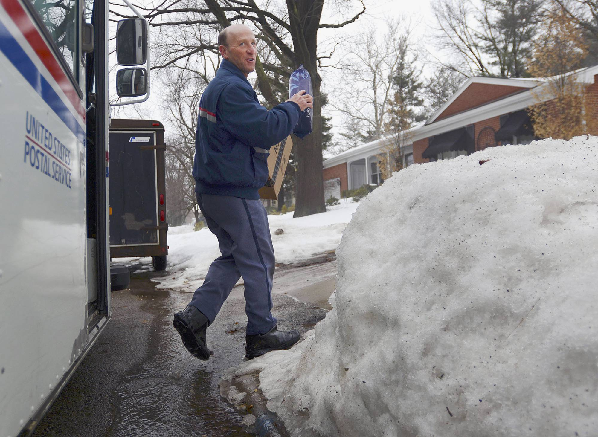 U.S. Postal Service letter carrier Gary Keist prepares to make a delivery to a home in Normal, Ill. Keist, 56, began as a letter carrier in 1978 and said this winter is the worst he's ever worked because of the consistent pattern of snowfalls followed by bitterly cold temperatures with little or no break.