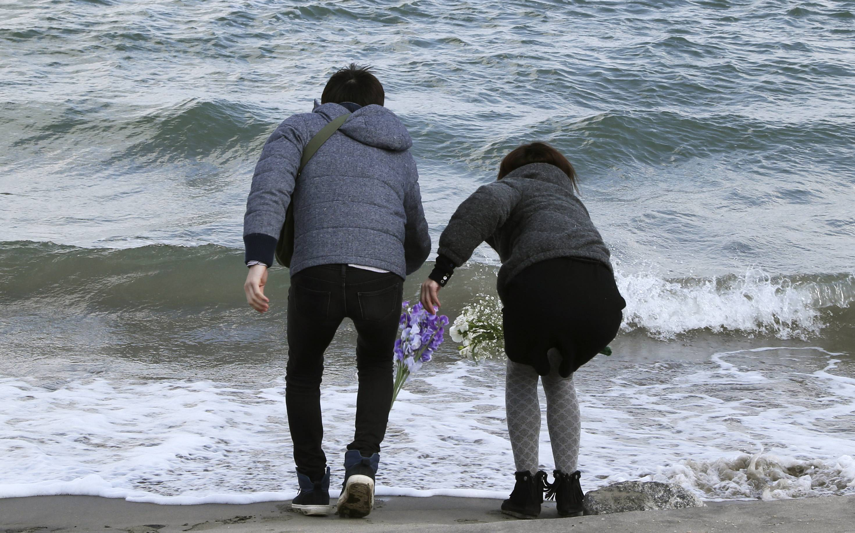 Employees of a nursing home Tsutomu Sato, 34, left, and Yoko Katayama, 30, toss bouquets of flowers into the sea in remembrance of the 36 people who died in the home during the March 11, 2011, earthquake and tsunami in Minamisoma Fukushima Prefecture, northeastern Japan, Tuesday, March 11 2014.