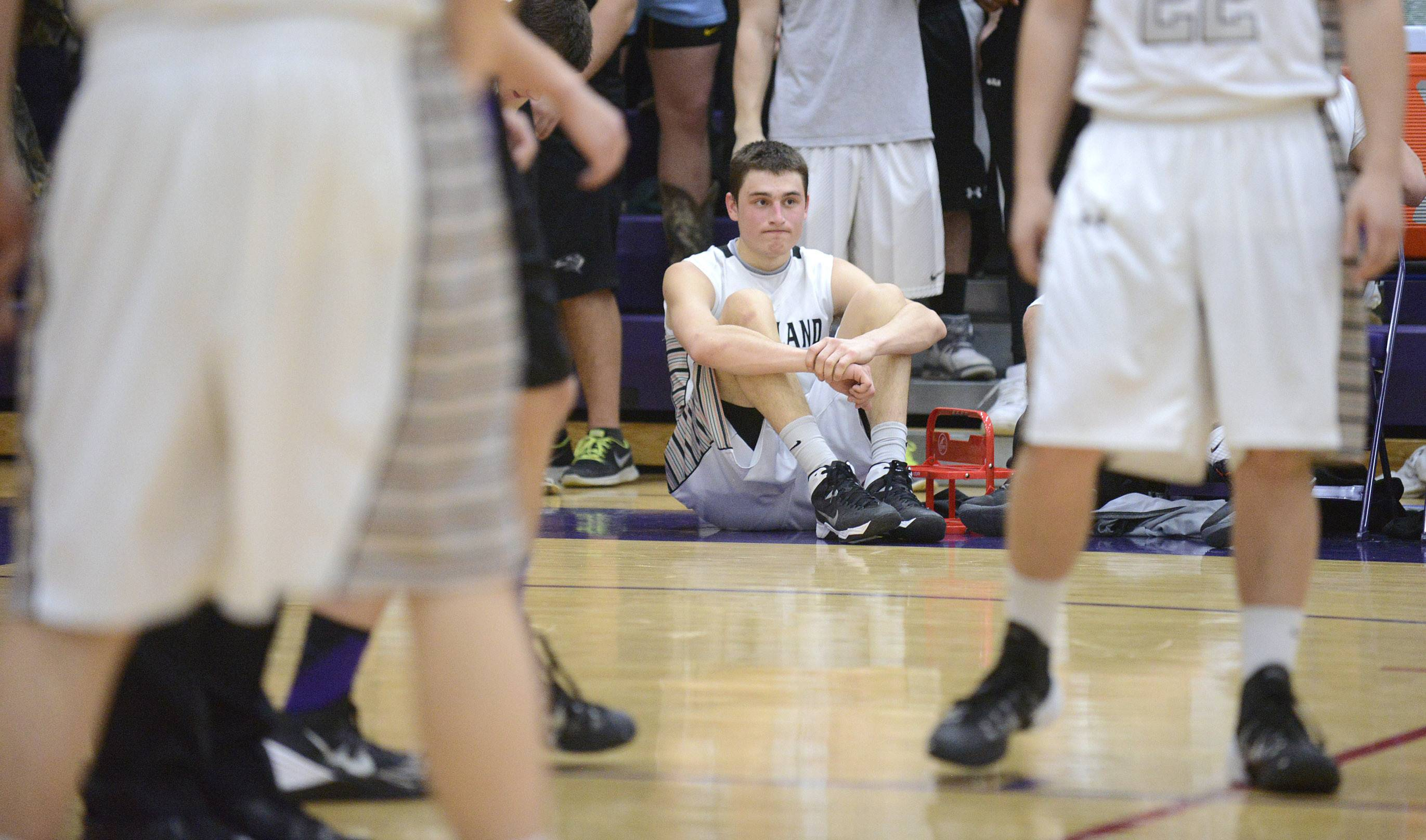 Kaneland's John Pruett sits at the end of the bench watching the final seconds of the game.