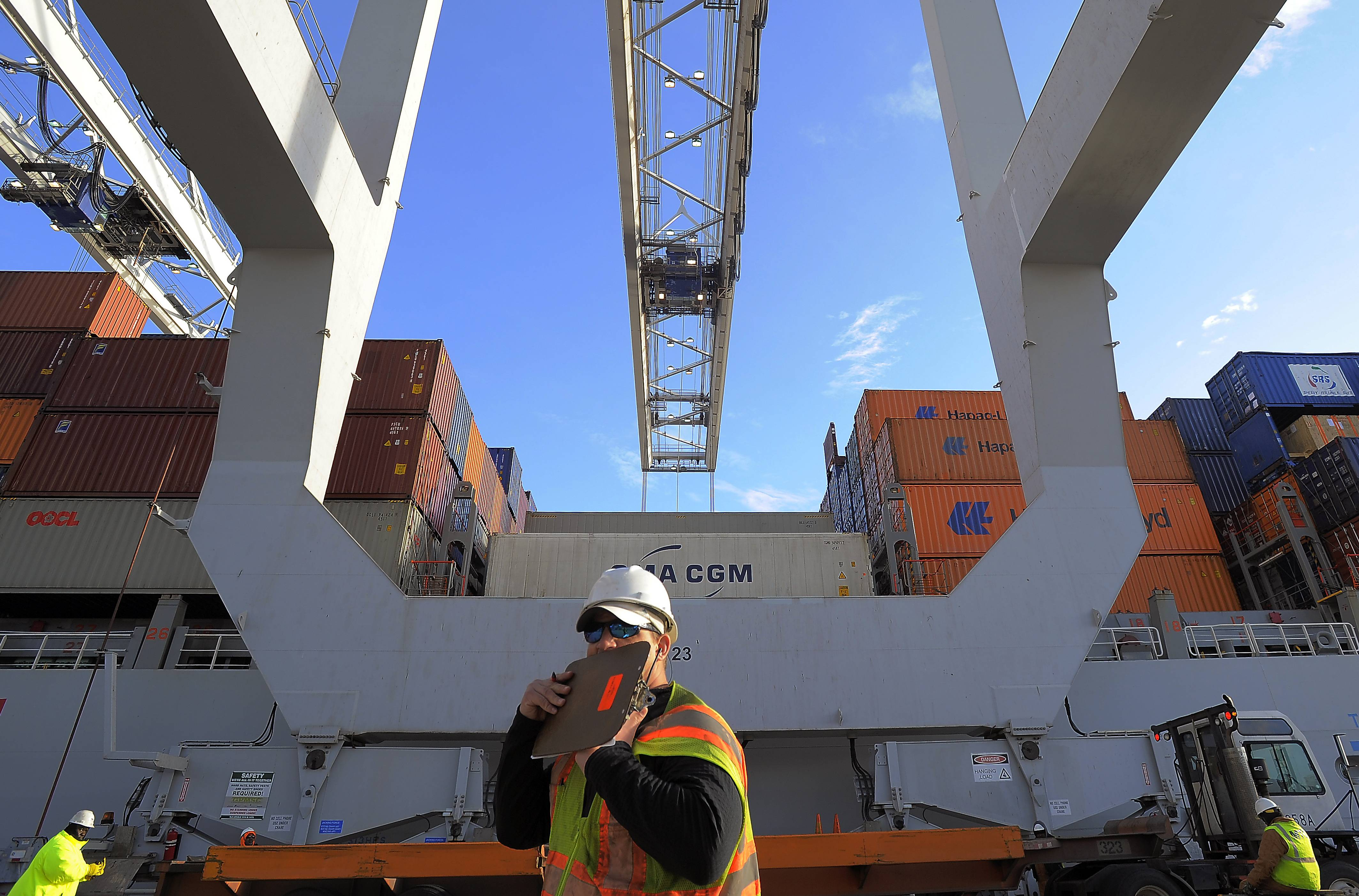 A dock worker communicates on a walkie-talkie while a ship to shore crane loads containers onto a ship at the Georgia Ports Authority Garden City terminal, in Savannah, Ga.  U.S. wholesale businesses in January suffered their steepest sales drop in nearly five years, yet they continued to increase their stockpiles.