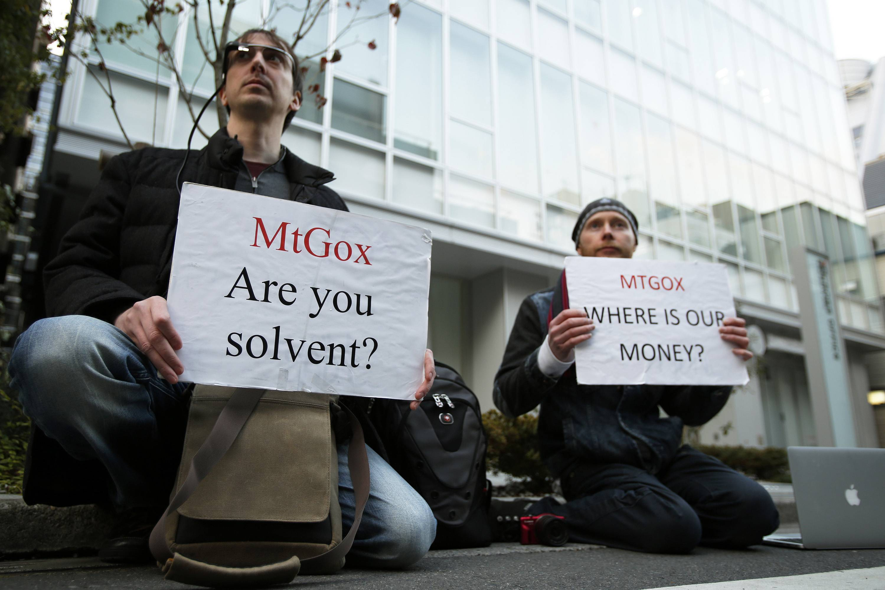 Kolin Burges, right, and another Mt. Gox customer hold placards while protesting outside a building housing the headquarters of Mt. Gox and its parent company Tibanne Co. in Tokyo, Japan.