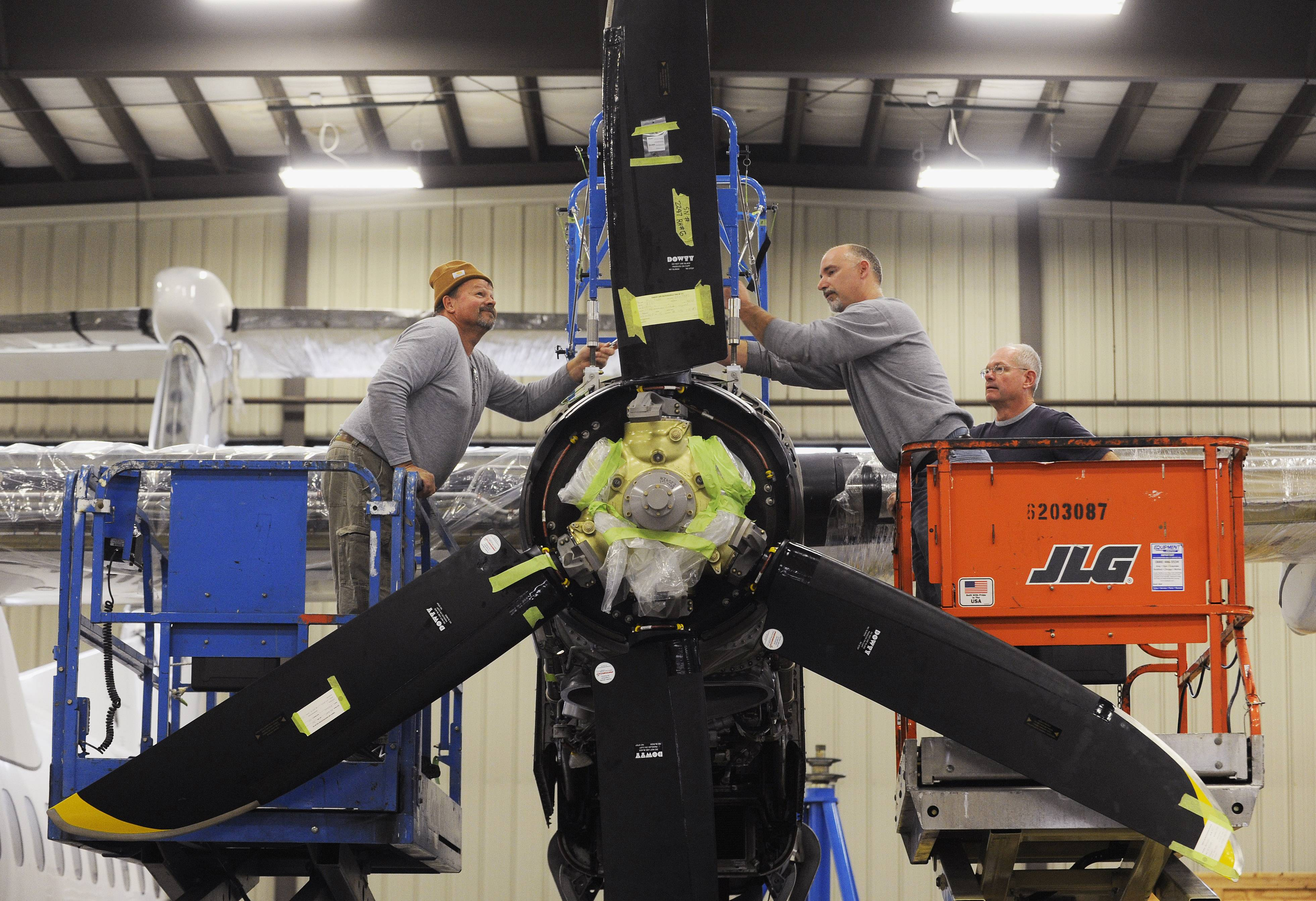Jerry Hampton, left, grabs a wrench from Brian Ward while doing maintenance at Emery Air Inc., in Rockford on the engine of a plane brought in from Columbia, Ill.