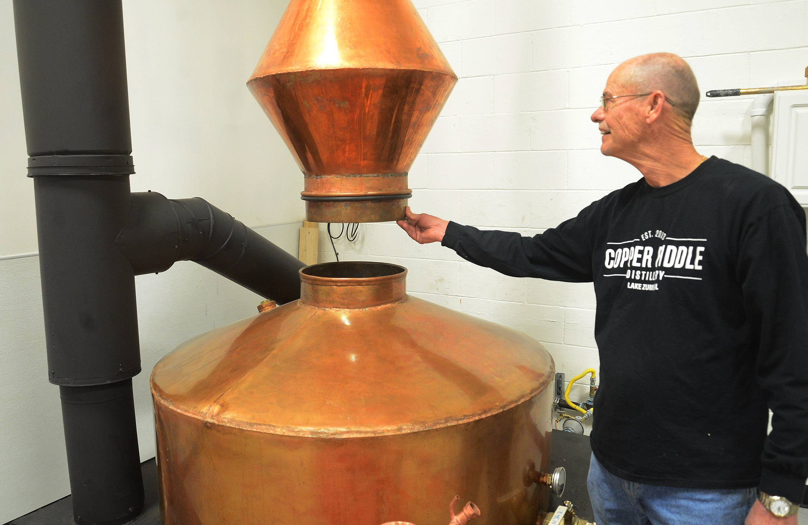 "Fred Robinson, co-owner of Copper Fiddle Distillery in Lake Zurich, shows off ""Big Al,"" a copper that took a year to be made in Arkansas for the business."