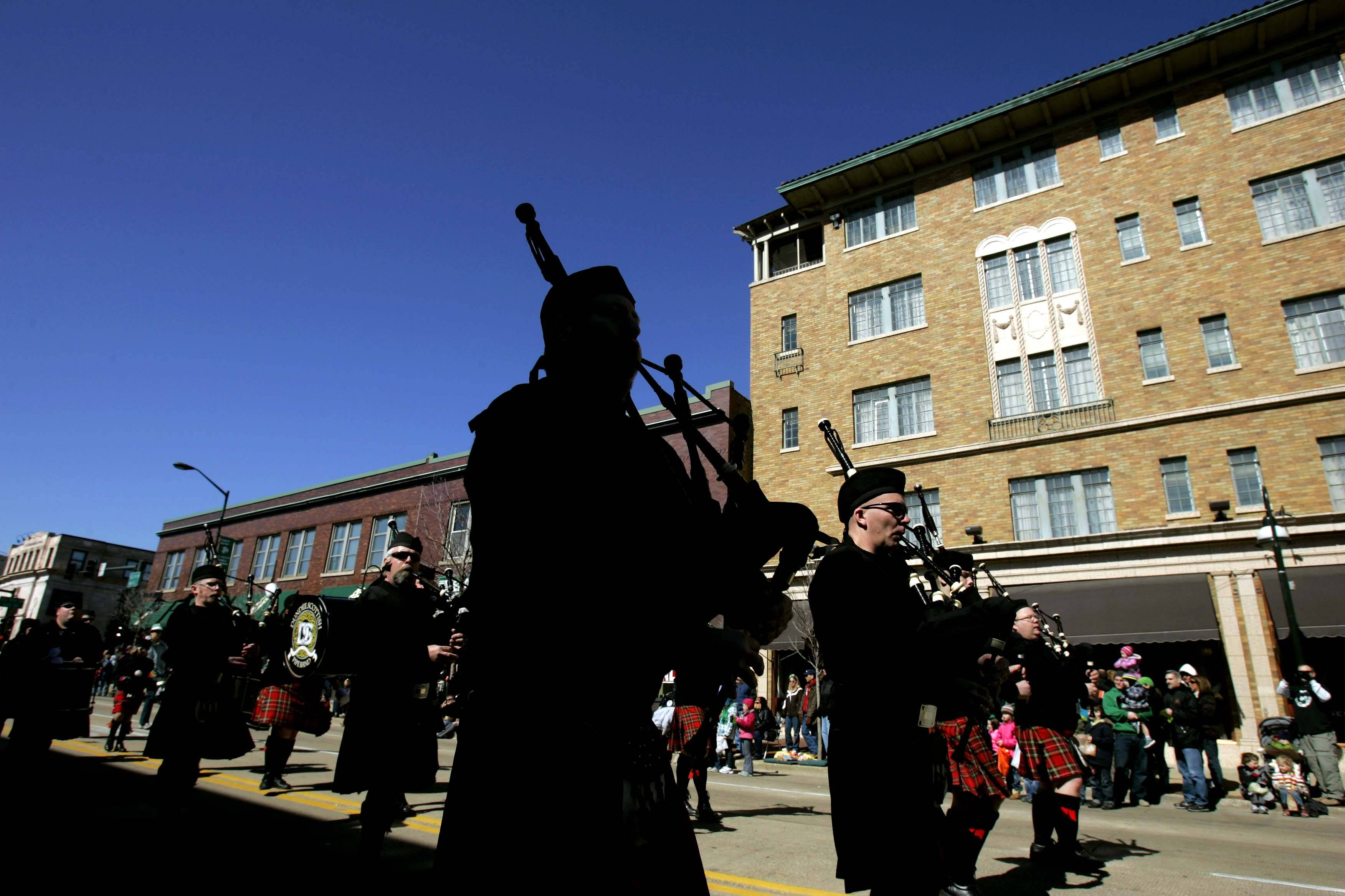 The Dundee Scottish Pipe Band plays as it passes in front of the Hotel Baker during the 2012 St. Patrick's Day parade in downtown St. Charles.