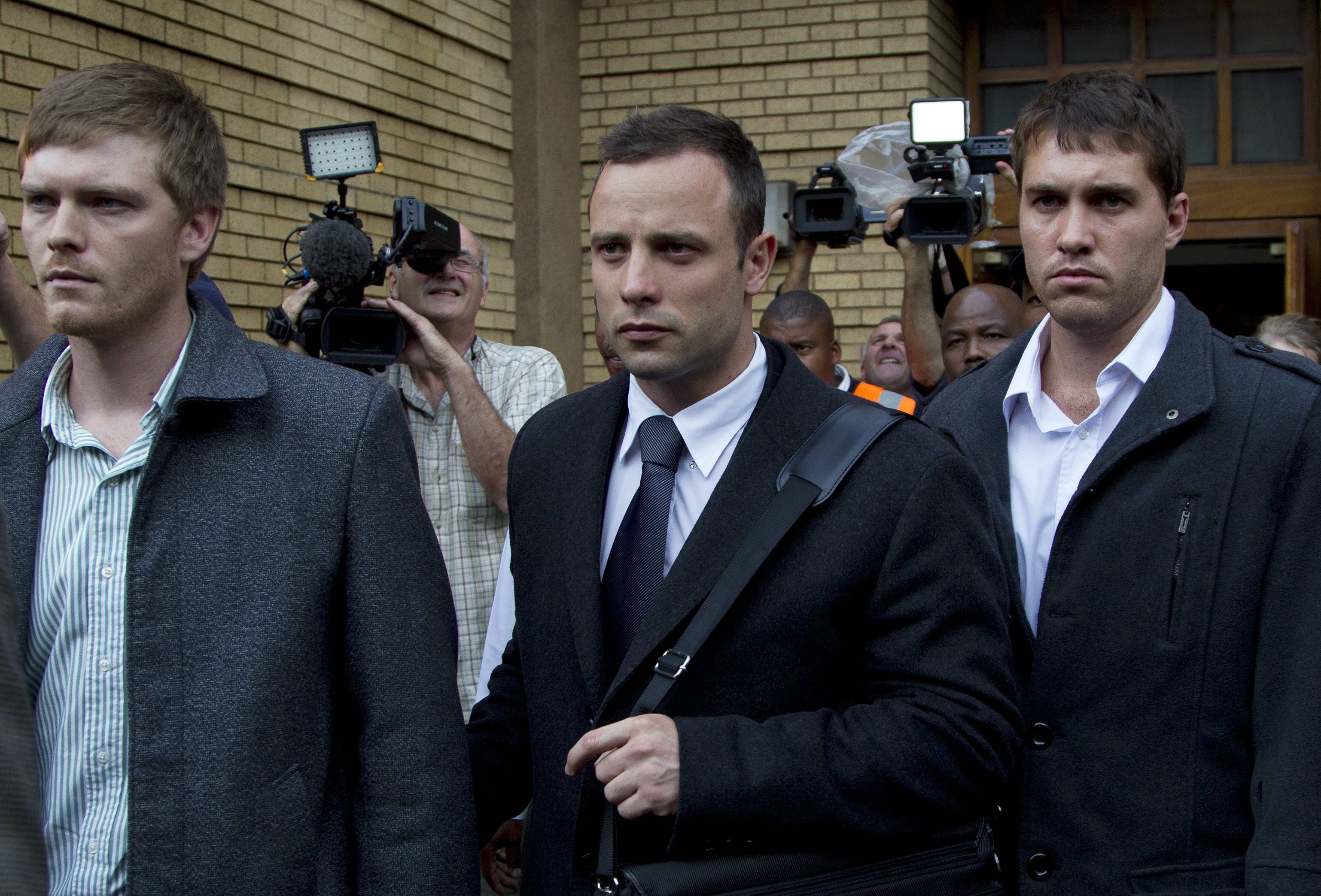 Oscar Pistorius, center, with unidentified men leaves the high court in Pretoria, South Africa, Tuesday. Pistorius is charged with murder for the shooting death of his girlfriend, Reeva Steenkamp, on Valentines Day in 2013.