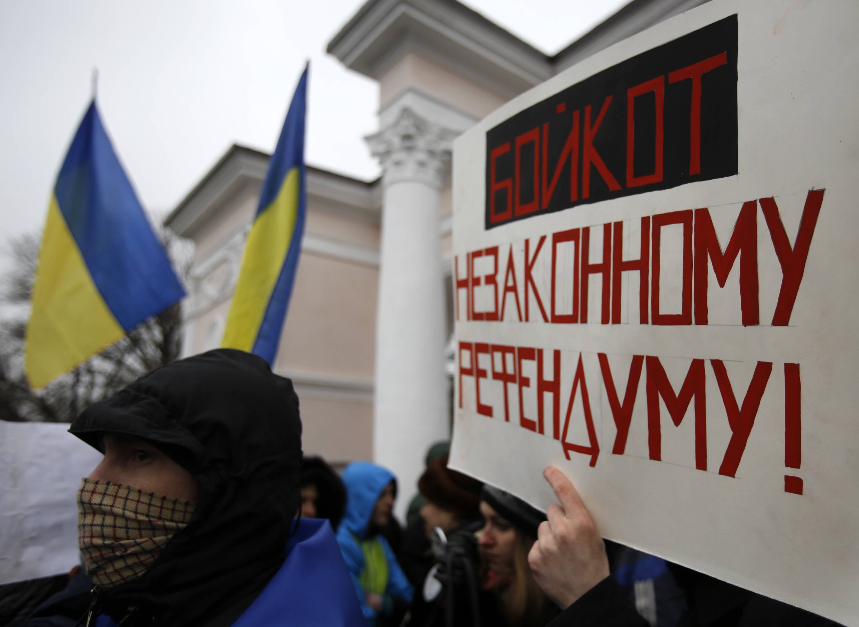 "A man holds a banner that reads: ""Boycott Illegal Referendum!"" during a rally against the breakup of the country in Simferopol, Crimea, Ukraine, Tuesday."