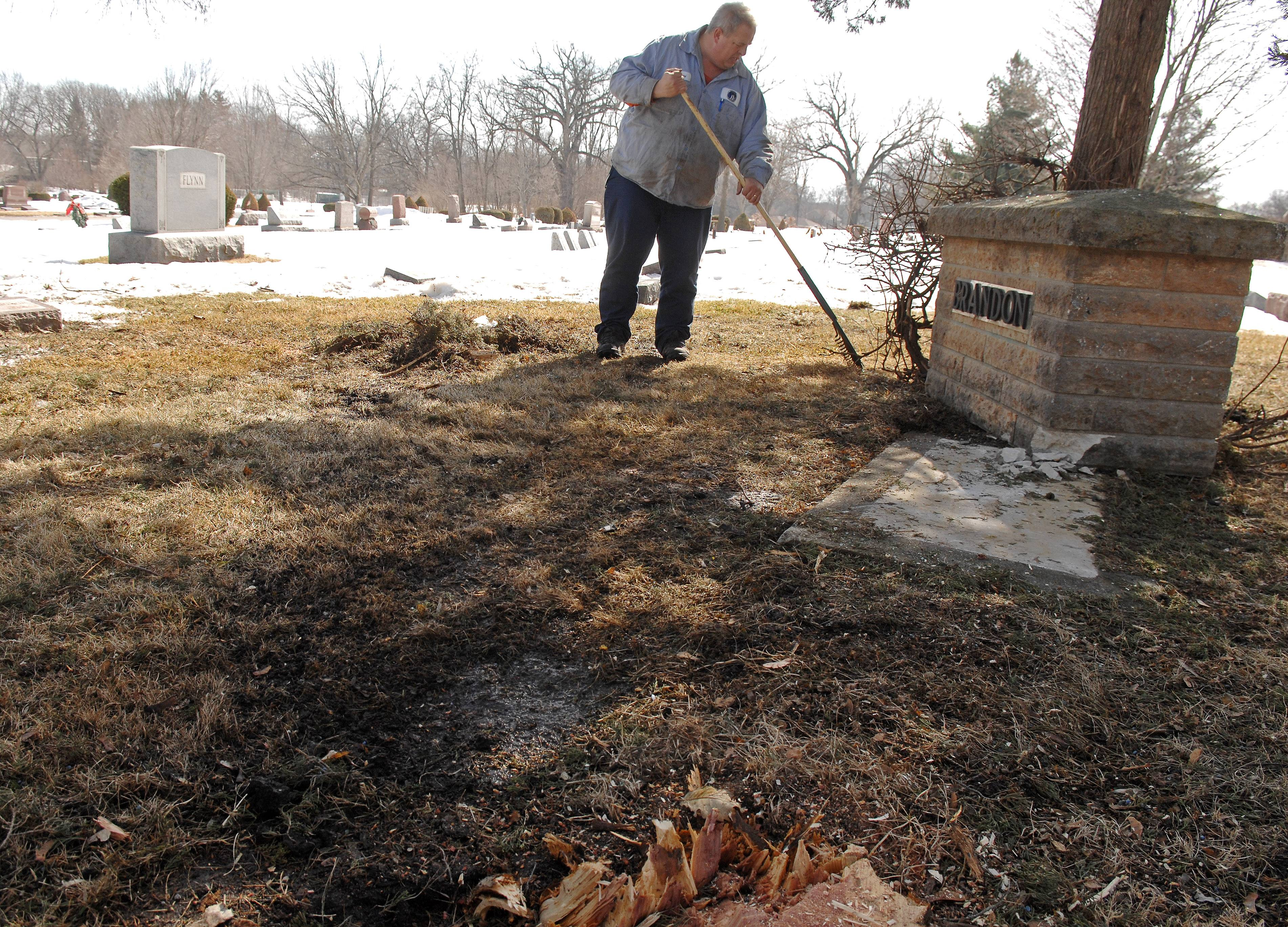 Wayne Gullickson of the Batavia Cemetery Department cleans the area of debris after a family marker was damaged and a cypress tree knocked over at West Batavia Cemetery by a drunken driver. Gullickson and a co-worker chipped up the tree earlier.