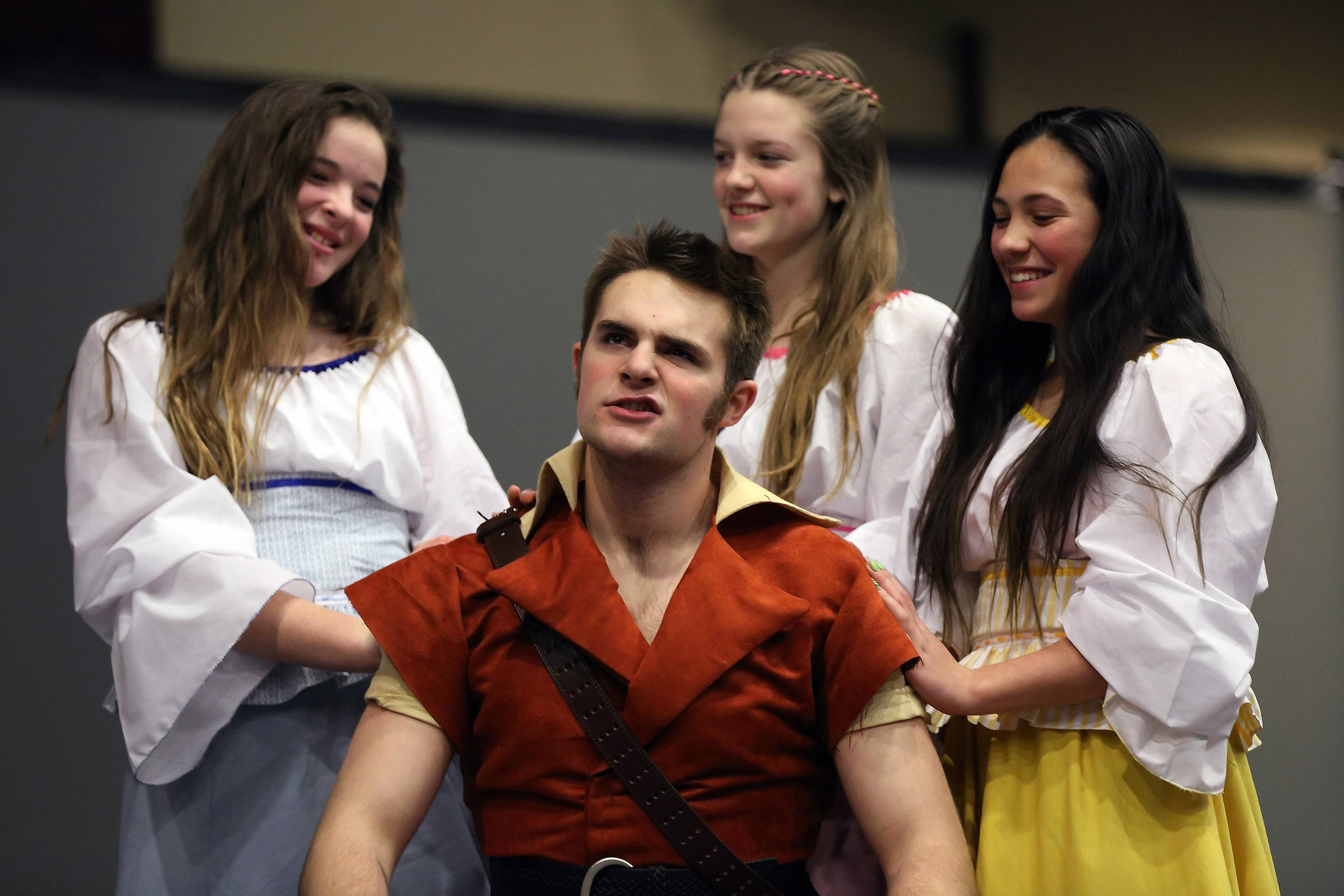 "The Silly Girls, from left, are Grace Wilken, Ariel Gray and Sonja Jenkins around Gaston played by Kurt Pazdra in the production of ""Beauty and the Beast"" at Harvest Christian Academy in Elgin."