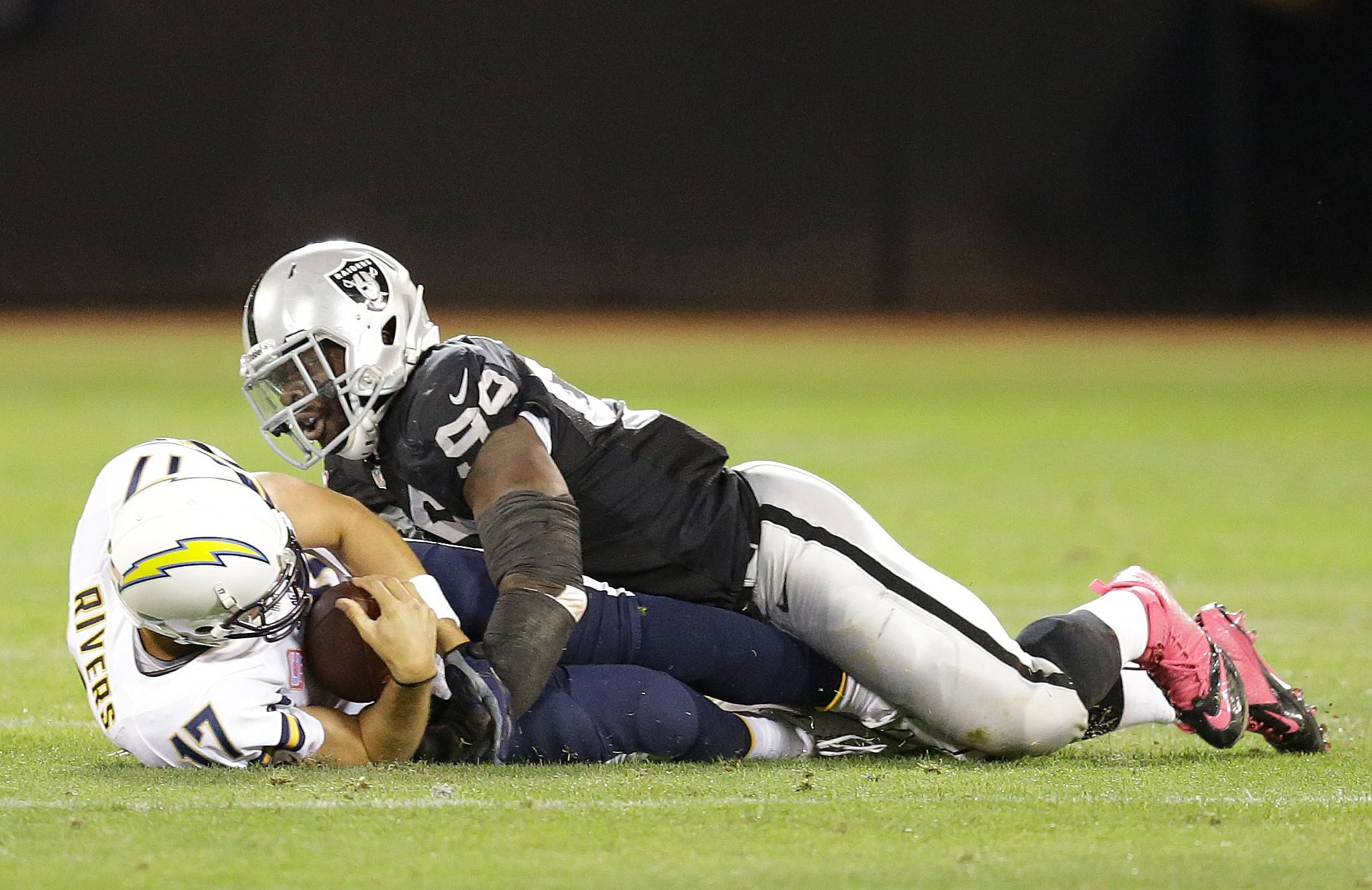 Oakland Raiders defensive end Lamarr Houston (99) lays on top of San Diego Chargers quarterback Philip Rivers (17) after sacking him during the second quarter of an NFL football game in Oakland, Calif., Sunday, Oct. 6, 2013.