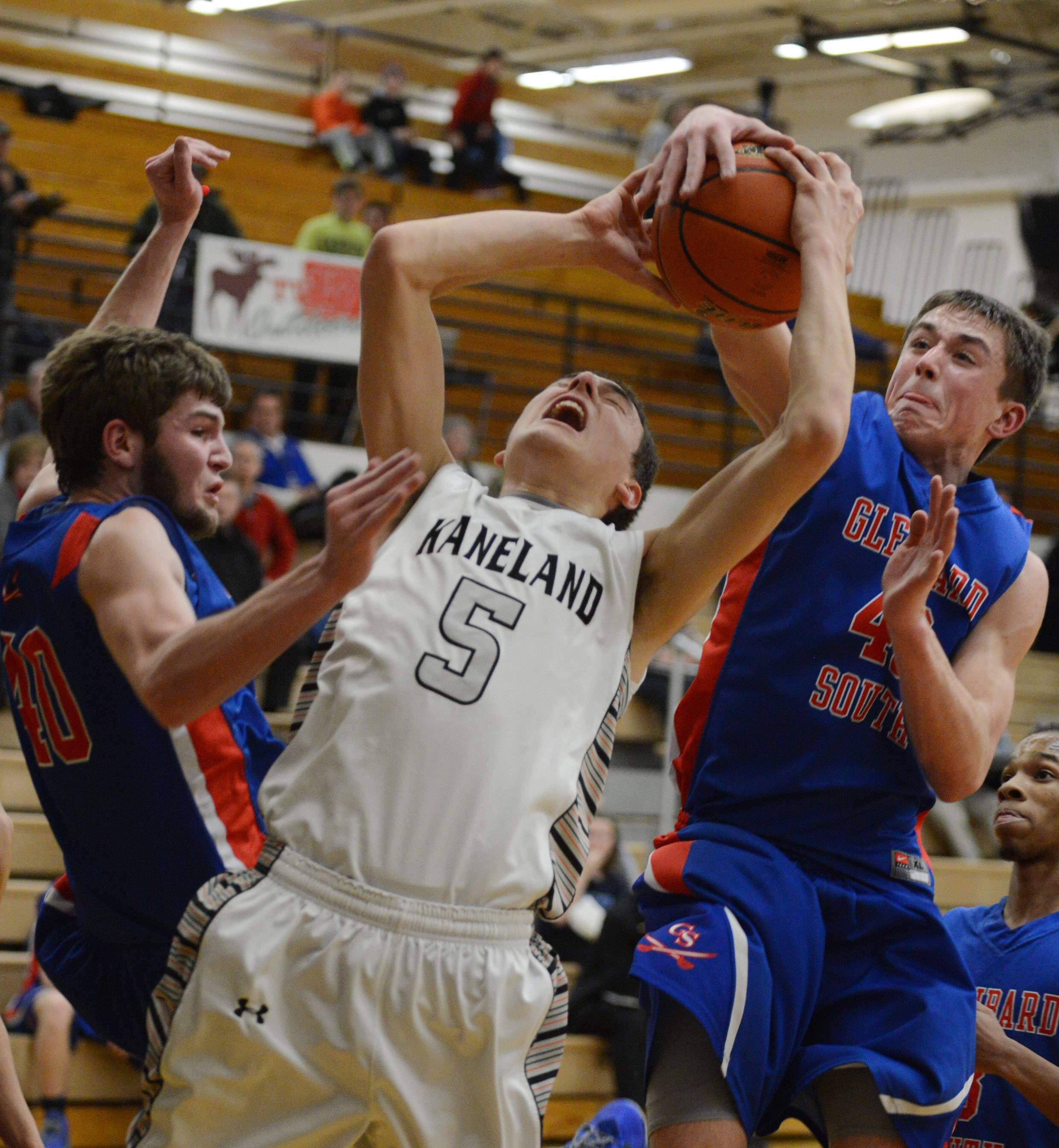 Kaneland's John Pruett (5) is fouled by Glenbard South's Billy Bair (42) during Tuesday's regional action at Kaneland.