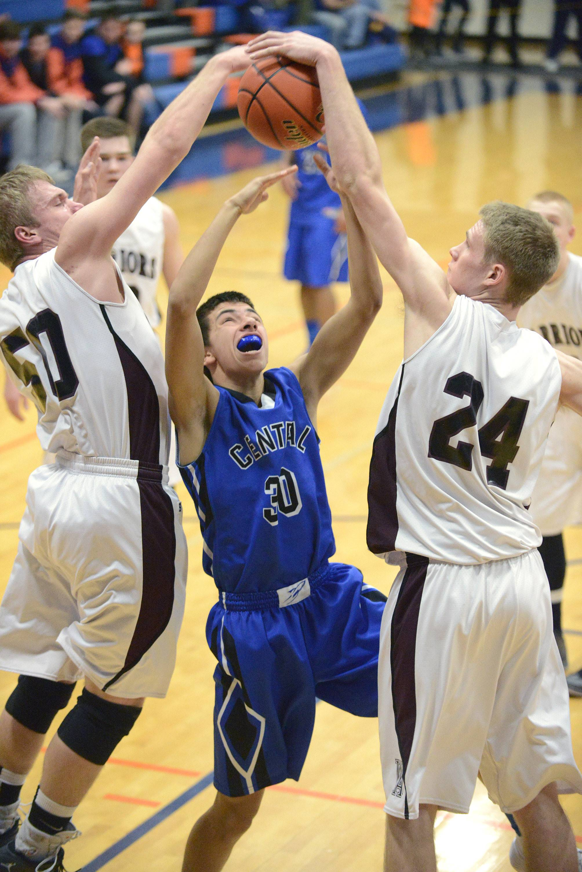 Burlington Central's James Raney is denied a basket by Wheaton Academy's Jacob Lindstedt, left, and Gordon Behr, right, during Wednesday's Class 3A regional game in Genoa.