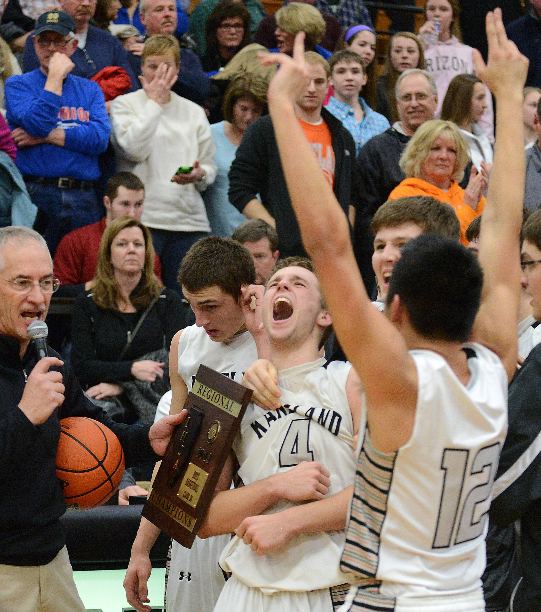 Kaneland players Drew David (4) and Ben Barnes (12) celebrate as they're awarded the championship plaque after winning Friday's regional title game in Maple Park.