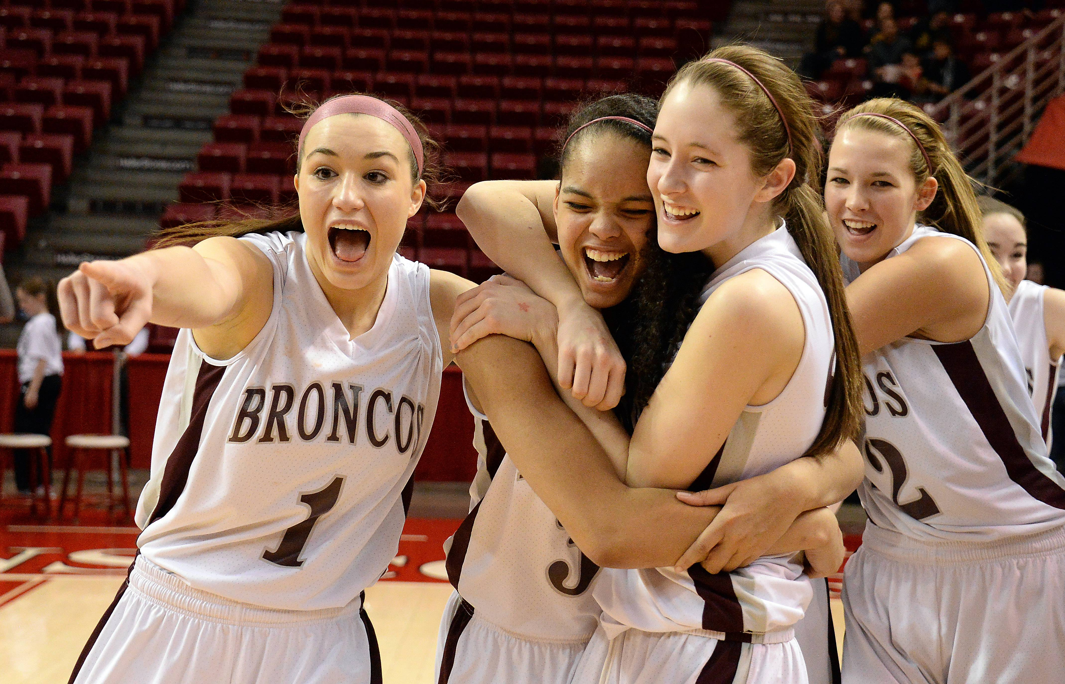 Montini players Kelsey Bogdan, Sara Ross and Kateri Stone celebrate after defeating Joliet Catholic Academy in the state girls basketball Class 3A championship game in Normal on Saturday.
