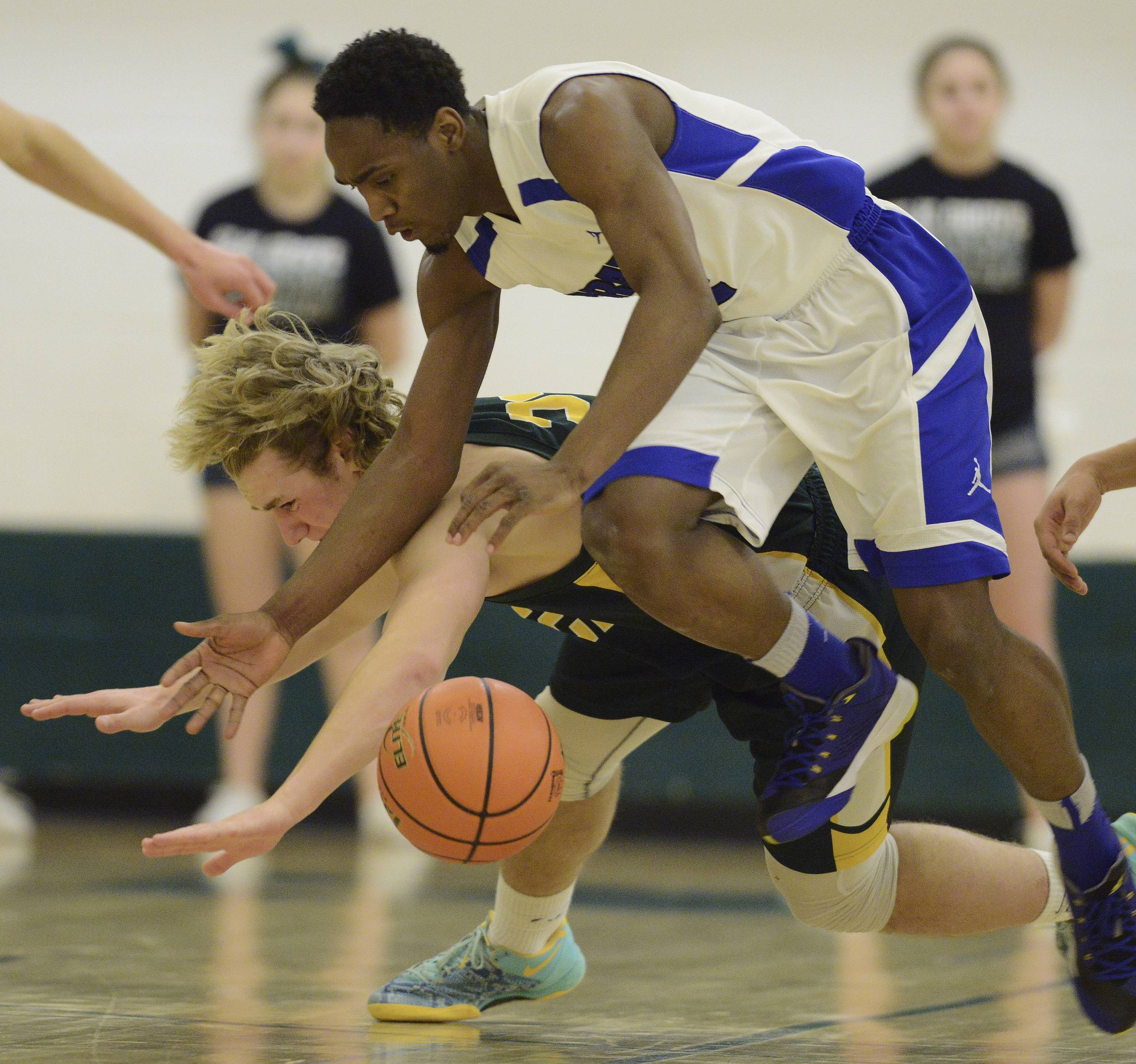 Elk Grove's Adam O'Malley, left, and Proviso East's Alano Span make contact while trying to control a loose ball during Tuesday's regional semifinal at Elk Grove High School.