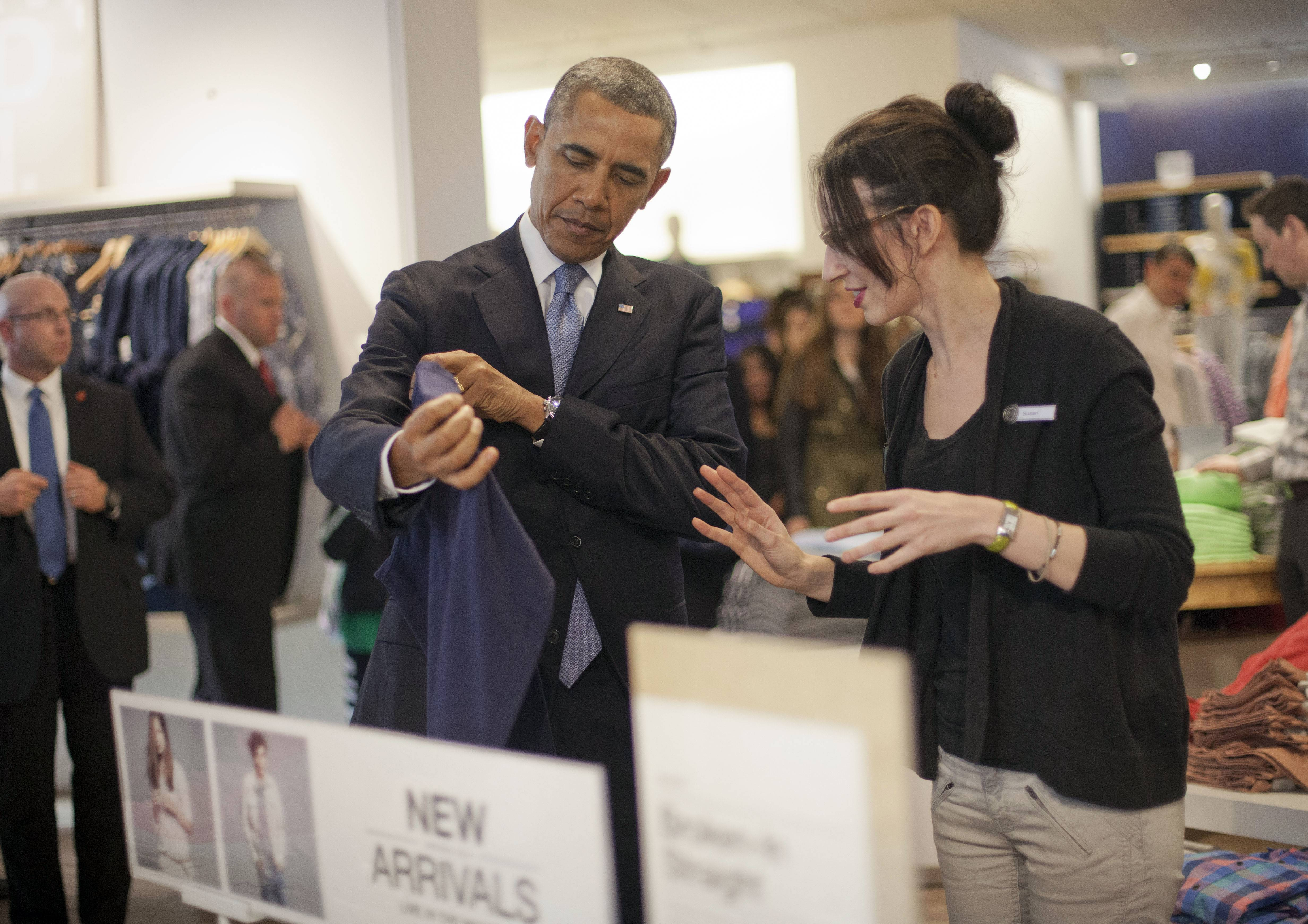 President Barack Obama, left, with the help of store employee Susan Panariello, right, shops at the GAP clothing store in Manhattan during his unannounced visit Tuesday in New York. Obama used the visit to talk about raising the minimum hourly wage standards and applauded the GAP, who earlier in the year announced it was raising minimum wage for its employees.