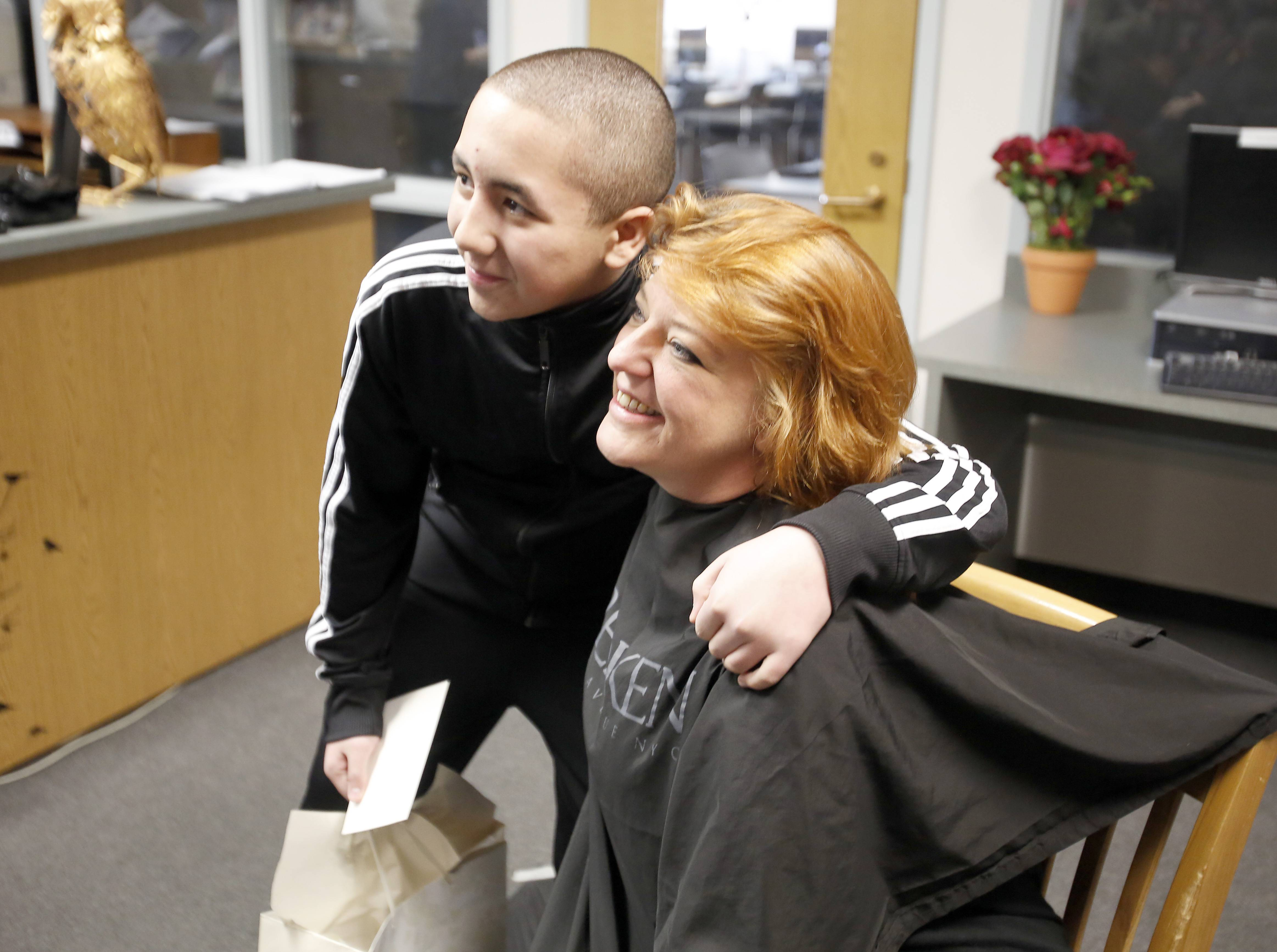 Ellis Middle School secretary Cyndi Downey poses Thursday with Christian Acevedo, an eighth-grader at Kenyon Woods Middle School in South Elgin, who's raising money for cancer research. Downey had her head shaved as part of the St. Baldrick's event at the Elgin school. The St. Baldrick's Foundation helps fund childhood cancer research.
