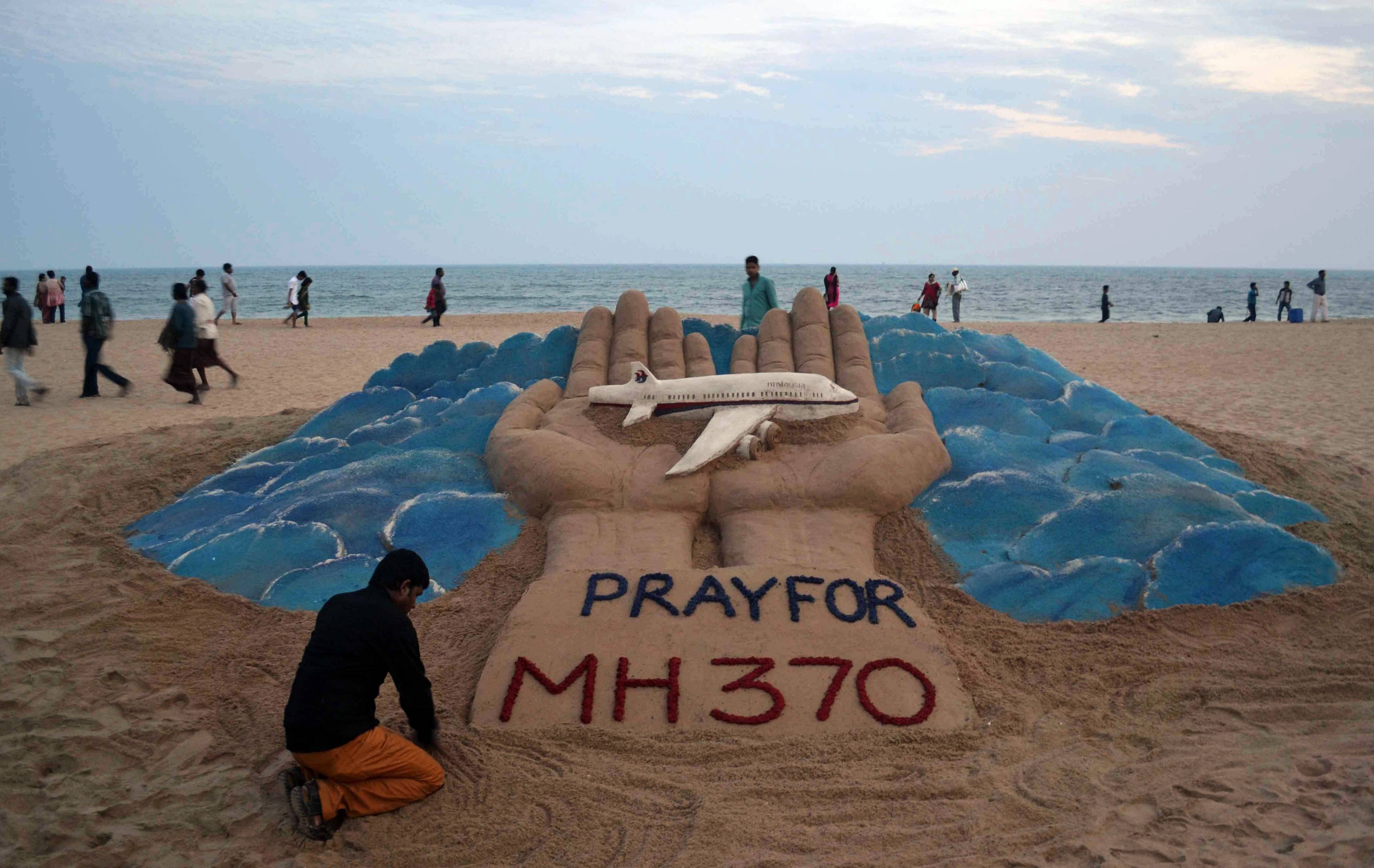 Sand artist Sudarshan Pattnaik creates a sculpture depicting the missing Malaysia Airlines aircraft on the beach in Puri, India, Wednesday, March 12, 2014. Malaysia has asked for India's assistance in searching for the missing Boeing 777 jetliner to widen the search to an area near the Andaman Sea, an Indian official said Wednesday.