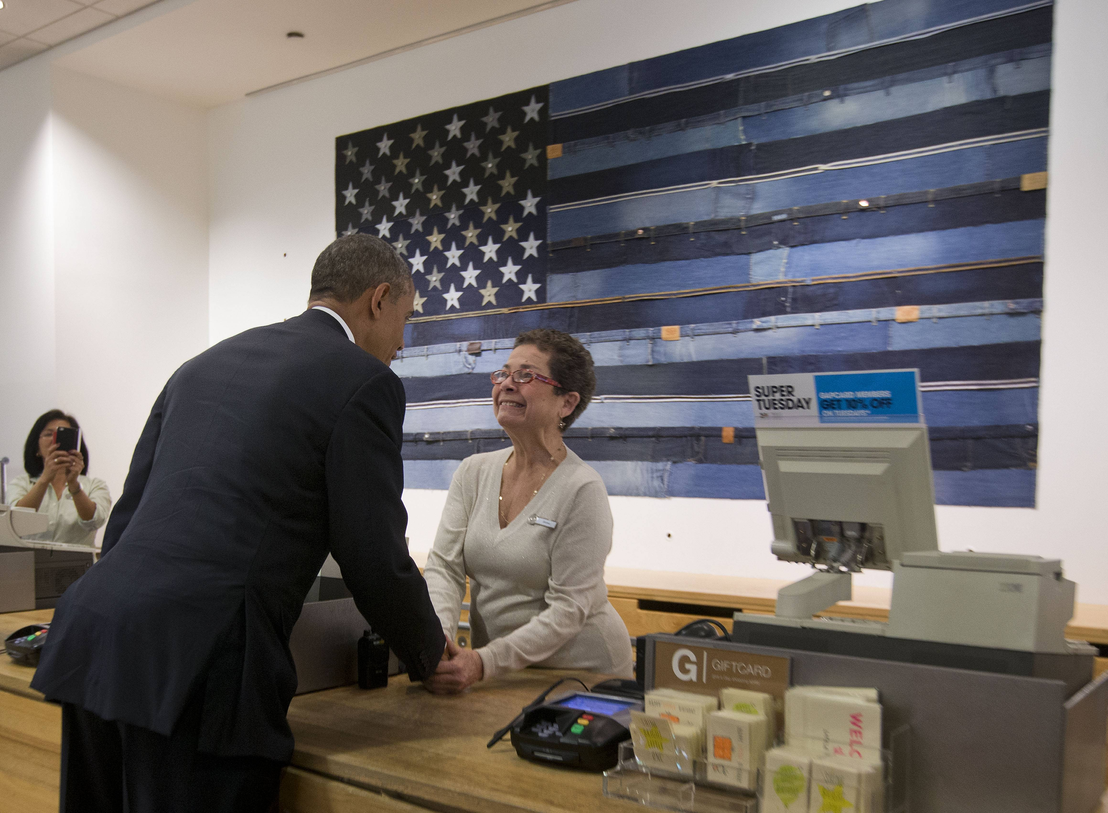President Barack Obama greets cashier Sonia Del Gatto at a GAP clothing store in Manhattan during his unannounced shopping visit, Tuesday. The White House is launching a campaign to promote a host of economic issues facing women, a key voting bloc in this year's midterm election.