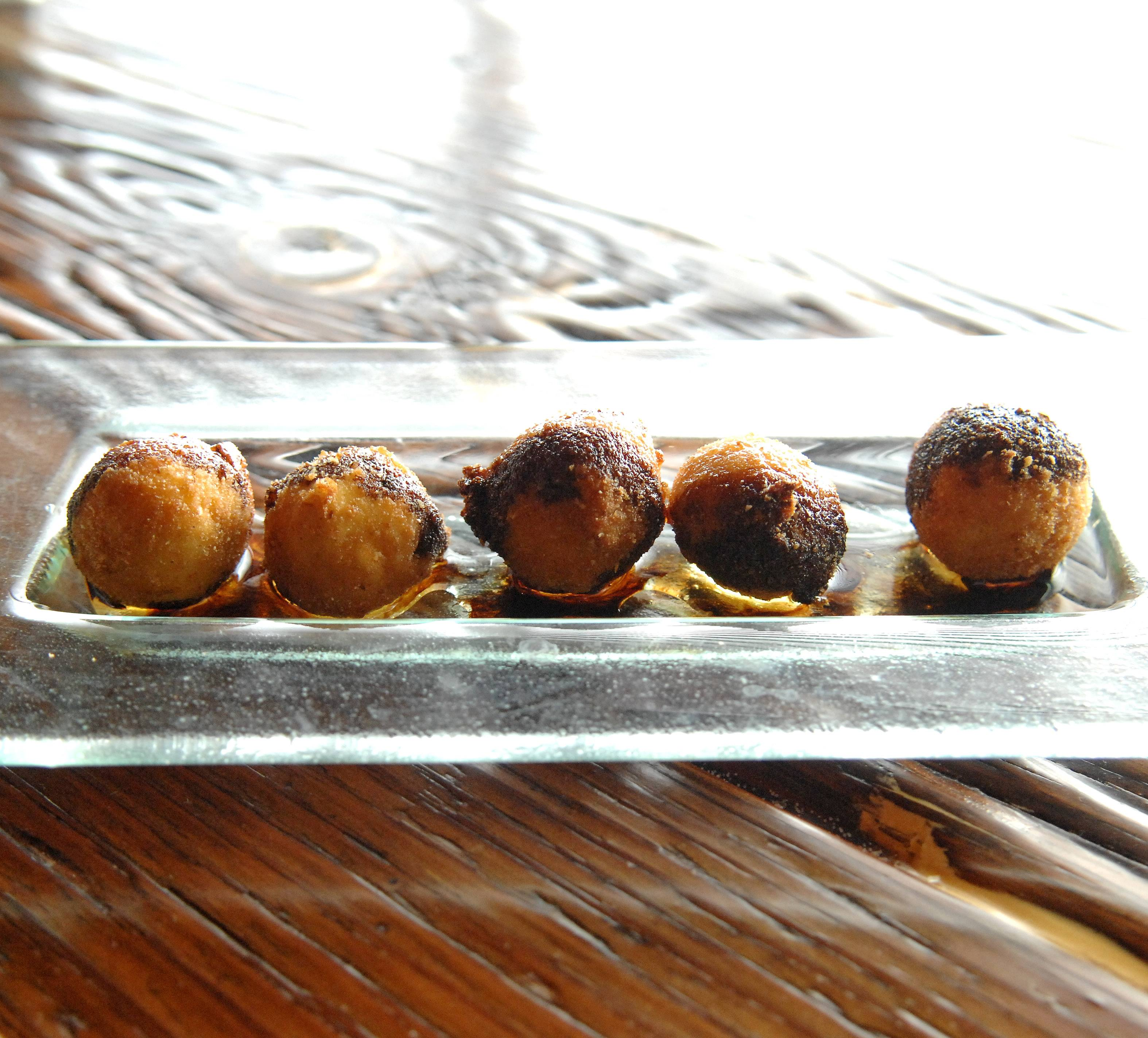 Croquetas de Queso de Cabra, or goat cheese fritters come topped with a honey and balsamic reduction at Macarena Tapas in St. Charles.