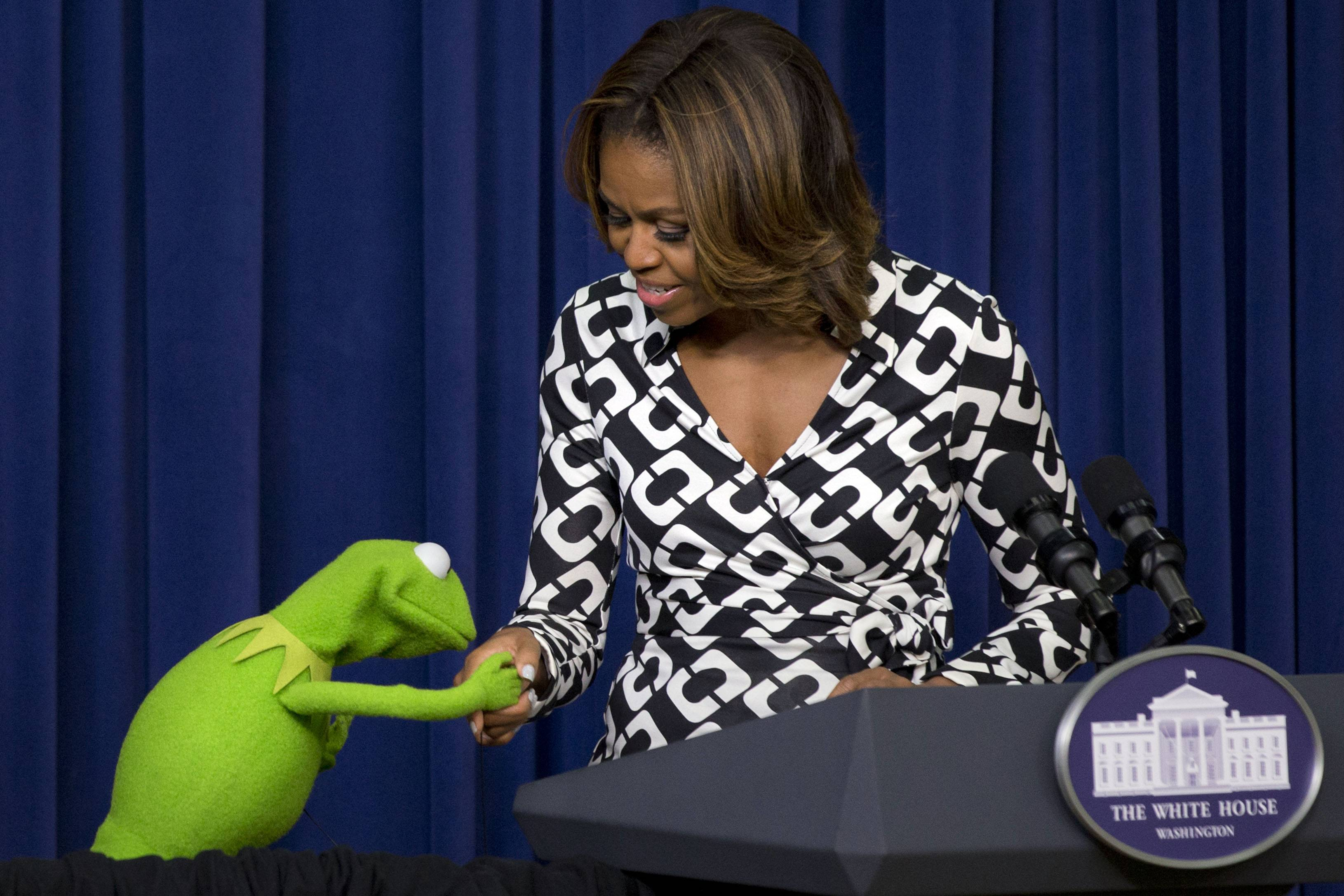 "Kermit the Frog kisses the hand of first lady Michelle Obama, during an event for children in military families in Washington Wednesday before a screening of Disney's ""Muppets Most Wanted"" movie as part of the Joining Forces initiative."