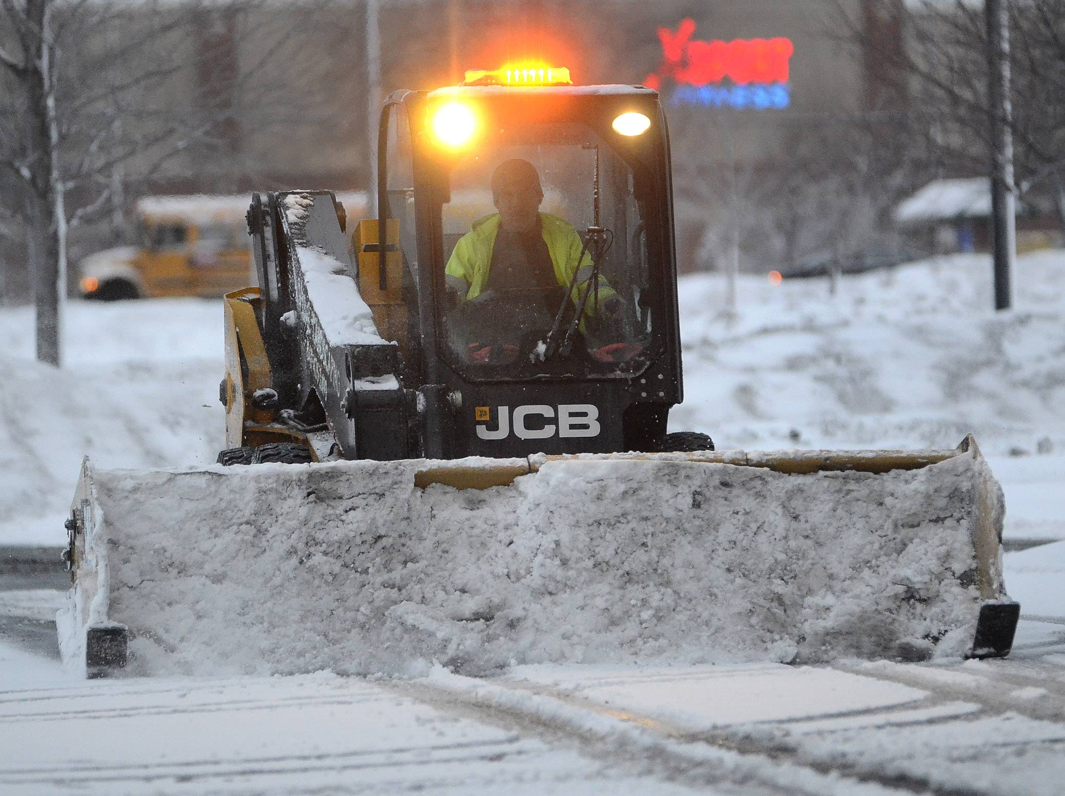 A snowplow clears an office building parking lot along Plaza Drive at Woodfield Mall.