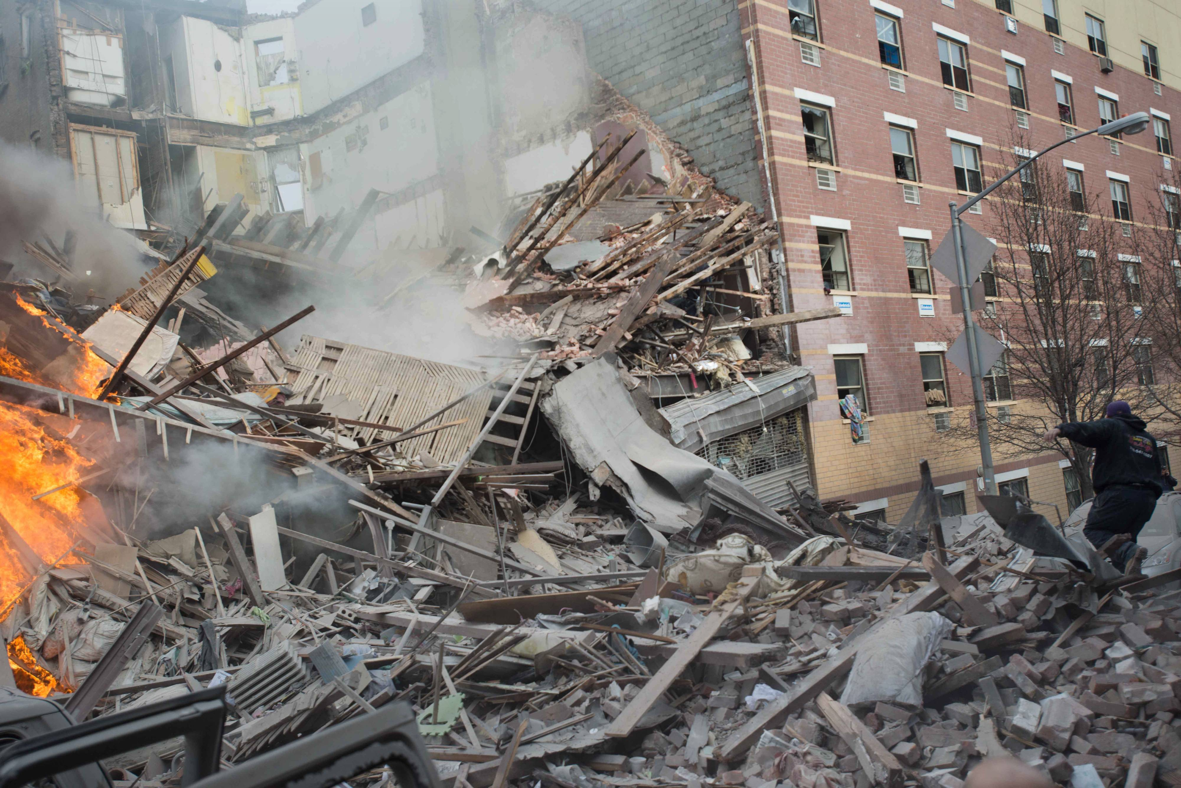 Emergency workers respond to the scene of an explosion and building collapse in the East Harlem neighborhood of New York, Wednesday, March 12, 2014. The explosion leveled two apartment buildings, and sent flames and billowing black smoke above the skyline.