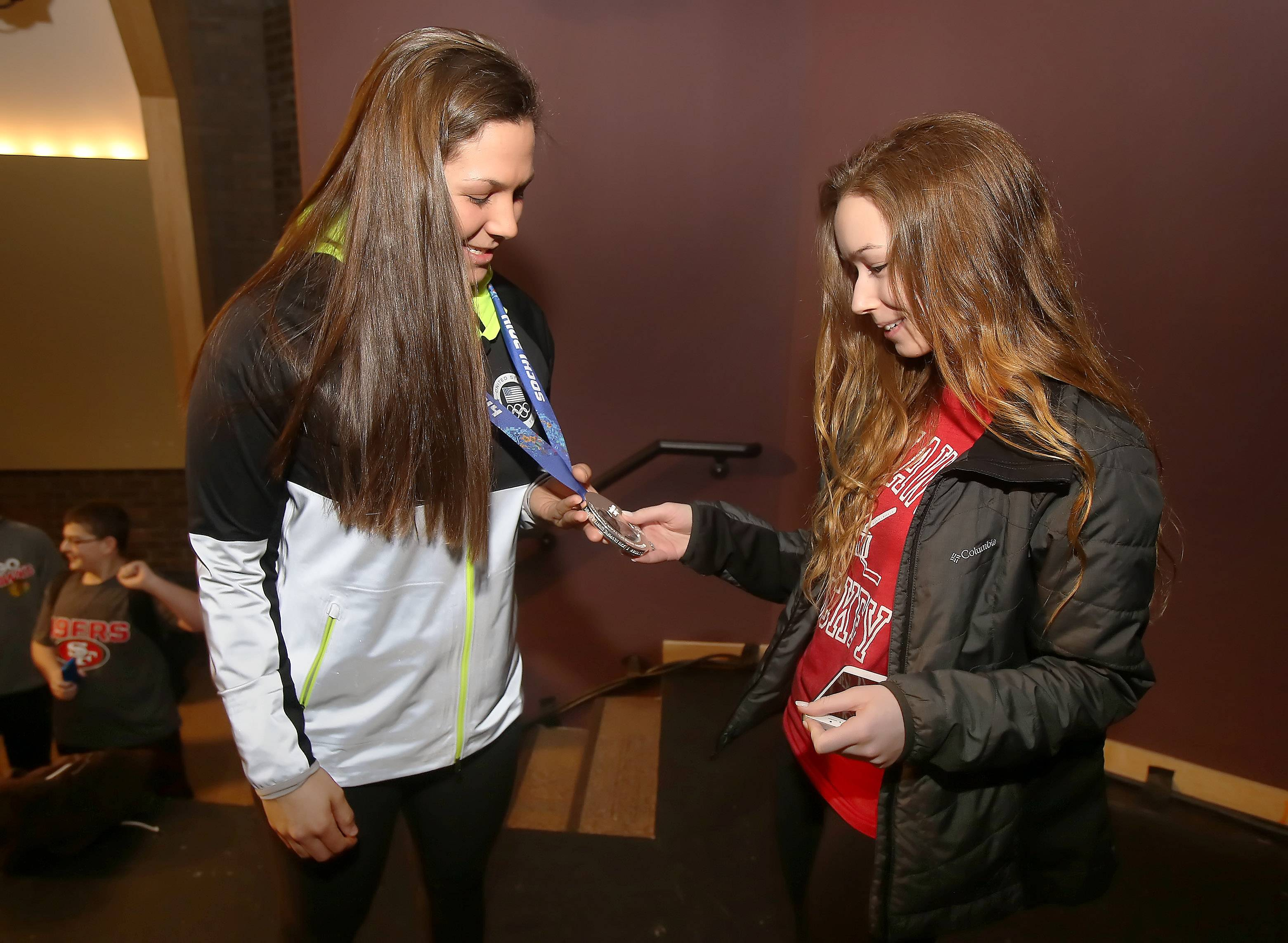 Olympian Megan Bozek, left, shows her silver medal to senior Lora Khalfin, as Bozek met with students and teachers Wednesday at Stevenson High School in Lincolnshire. The Stevenson graduate won the silver as a member of the U.S. women's ice hockey team in the 2014 Sochi Winter Olympics.