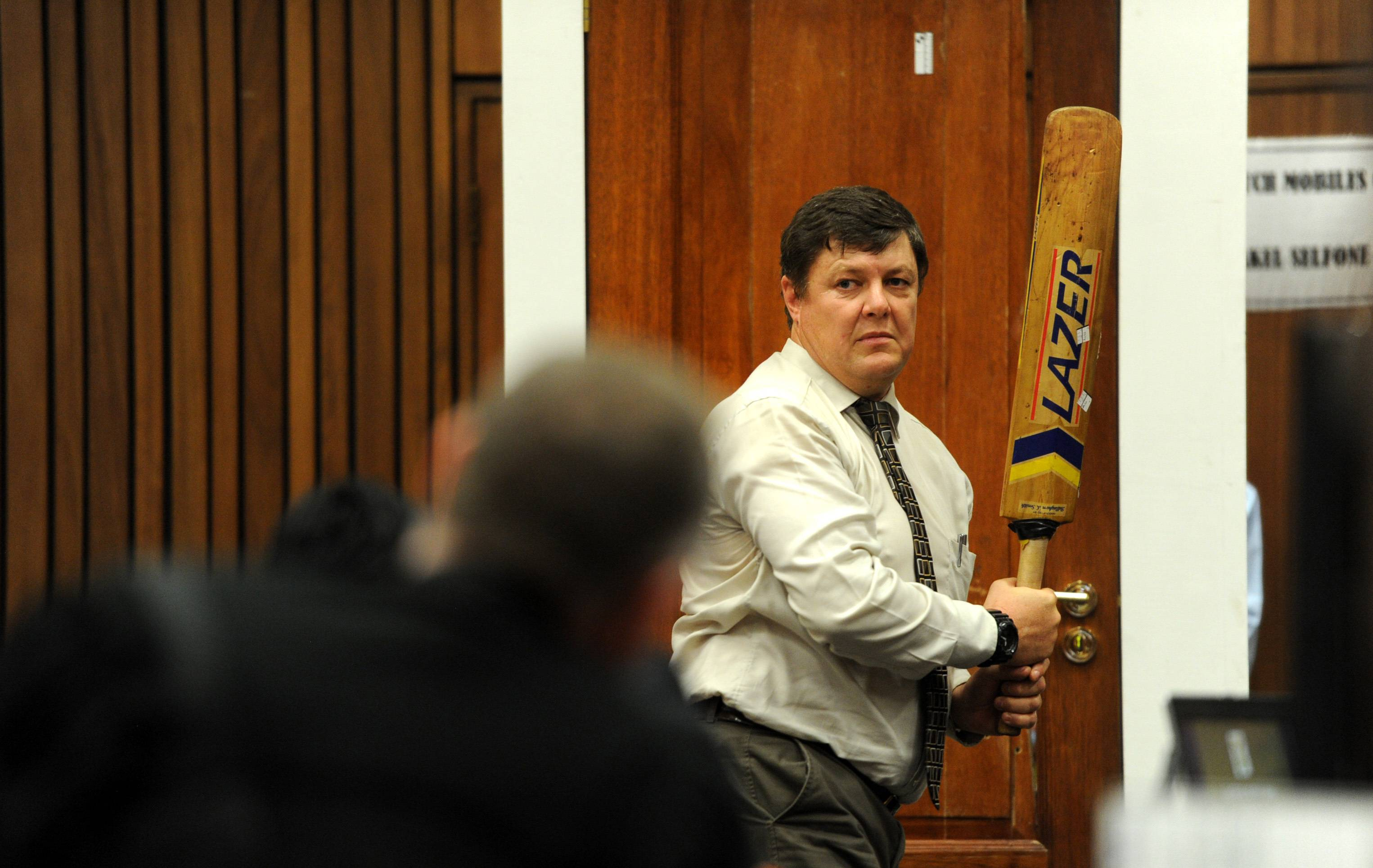 Forensic investigator Johannes Vermeulen, with a cricket bat in hand, demonstrates on a mock-up toilet cubicle, with the door, background, how the door could have been broken down with the bat, during the trial of Oscar Pistorius in court in Pretoria, South Africa, Wednesday. Pistorius is charged with the shooting death of his girlfriend Reeva Steenkamp, on Valentine's Day in 2013.