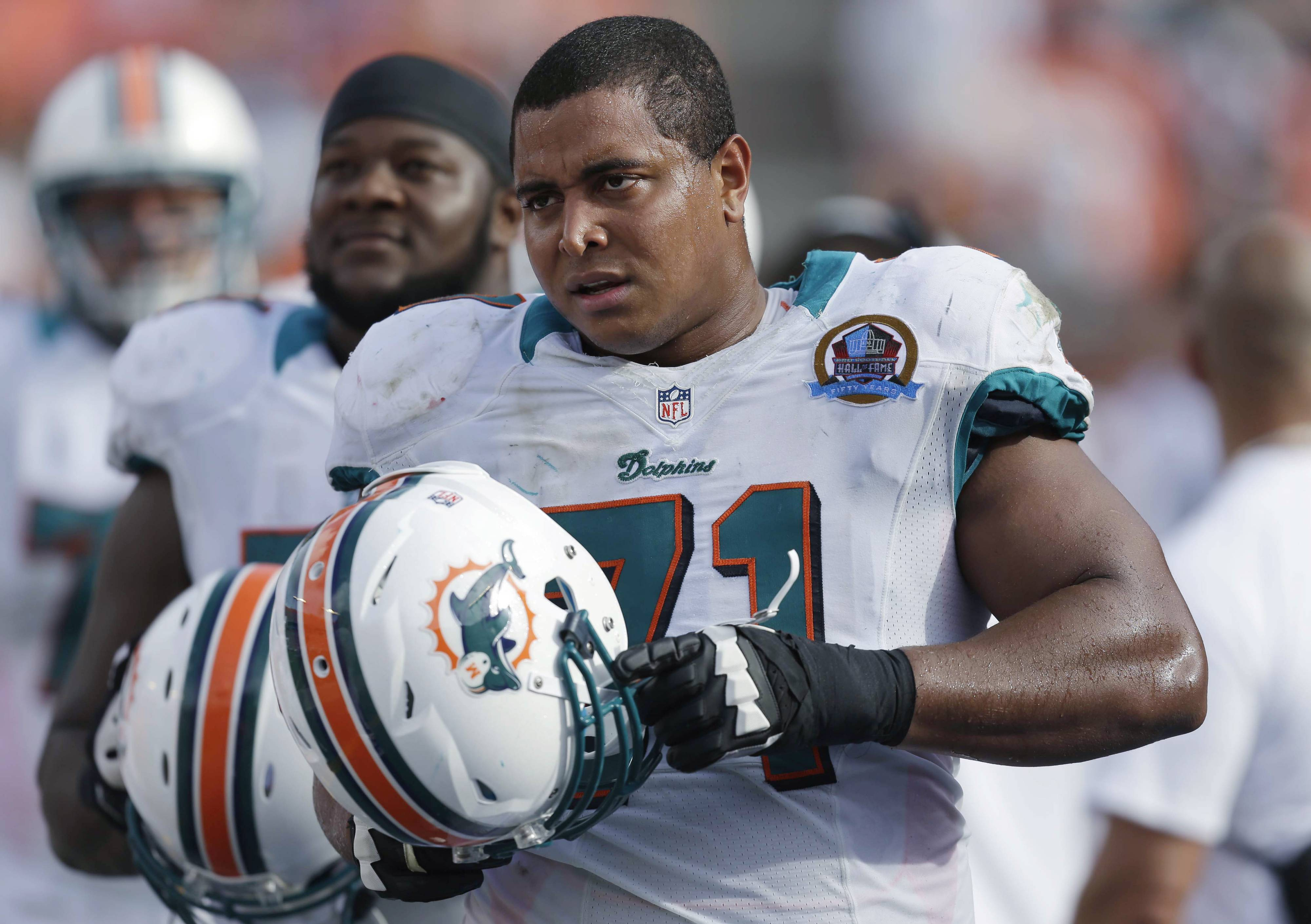 In this Dc. 16, 2012, photo, Miami Dolphins tackle Jonathan Martin (71) stands on the sidelines during the Dolphins' NFL football game against the Jacksonville Jaguars in Miami. Martin, the offensive tackle at the center of the Dolphins' bullying scandal, has been traded to the San Francisco 49ers. The Dolphins announced the deal Tuesday night, March 11, 2014, on the first day of NFL free agency. Martin's move cross country brings him back to the Bay Area to be reunited with his former Stanford coach, Jim Harbaugh.