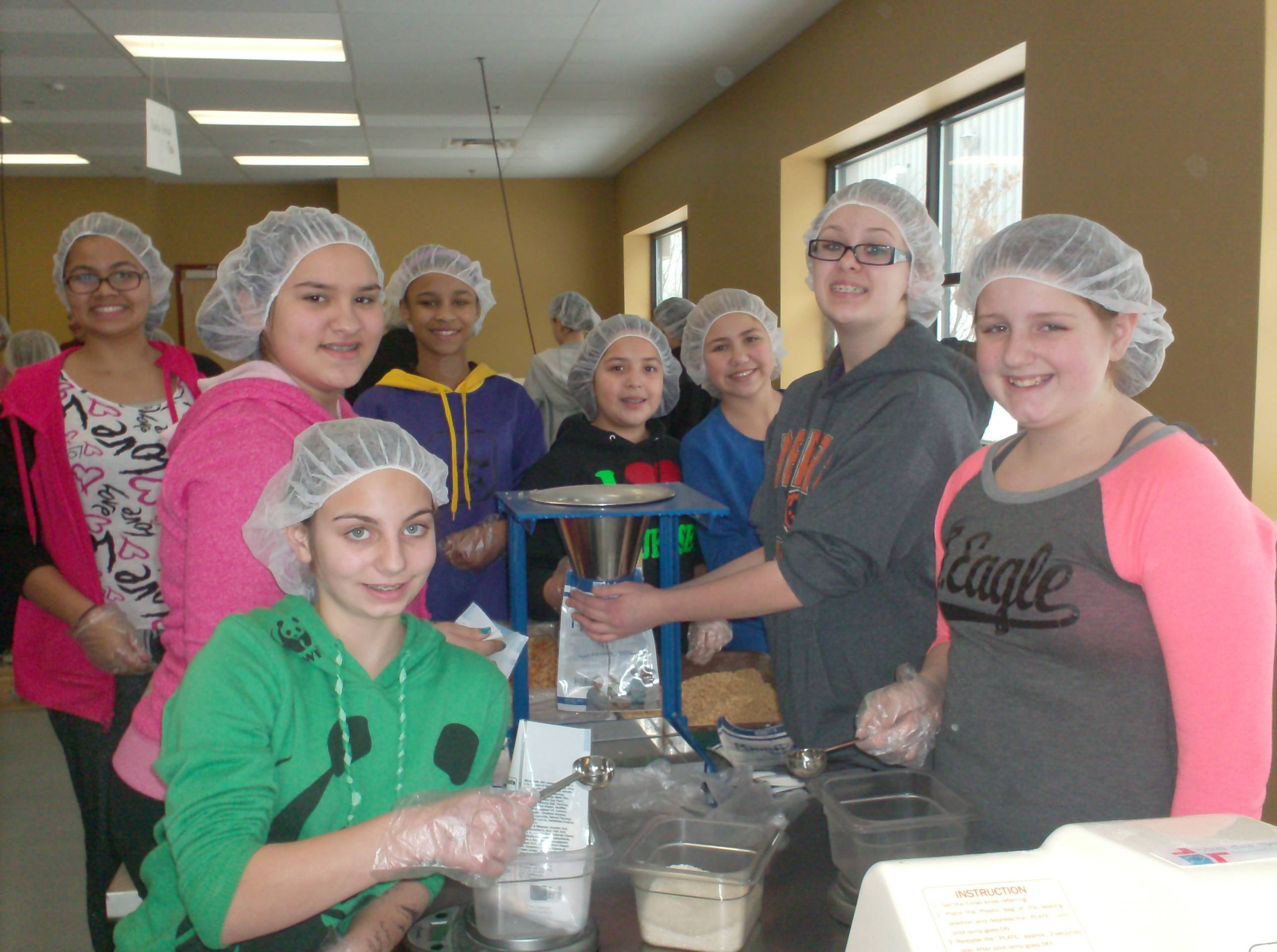 Matthews Middle School students packing food at the Feed My Starving Children facility in Libertyville