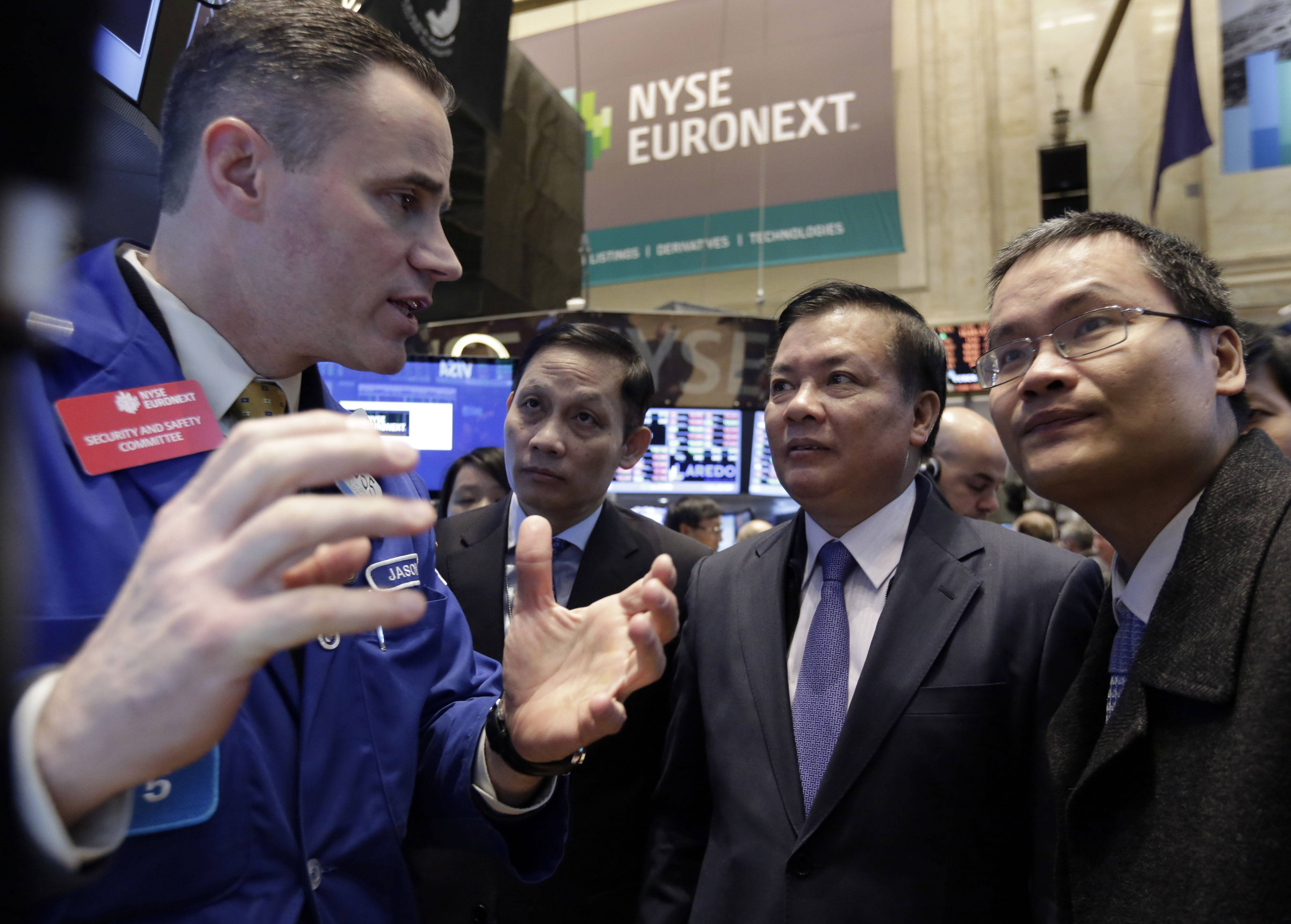 Vietnam's Finance Minister Dinh Tien Dung, second from right, visits the trading post of specialist Jason Hardzewicz on the floor of the New York Stock Exchange Thursday. Stocks fell, erasing this year's gains for the Standard & Poor's 500 Index, as weaker- than-forecast data from China and tension in Ukraine overshadowed reports showing an improving American economy.