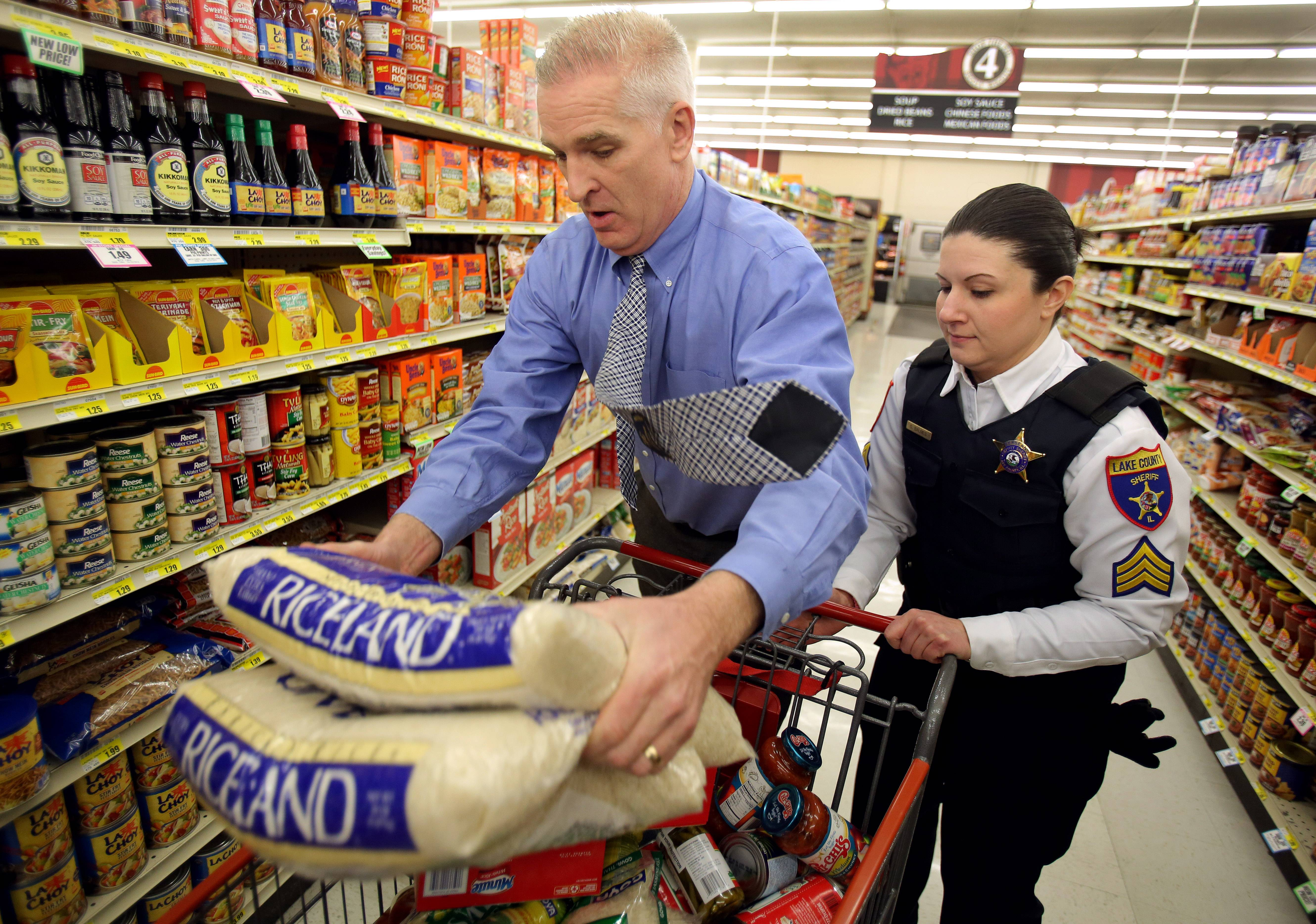 Lake County Sheriff Mark Curran, left, dashes through the aisles of Piggly Wiggly in Antioch with Lake County sheriff's Sgt. Sara Balmes in a race to collect food for local pantries.