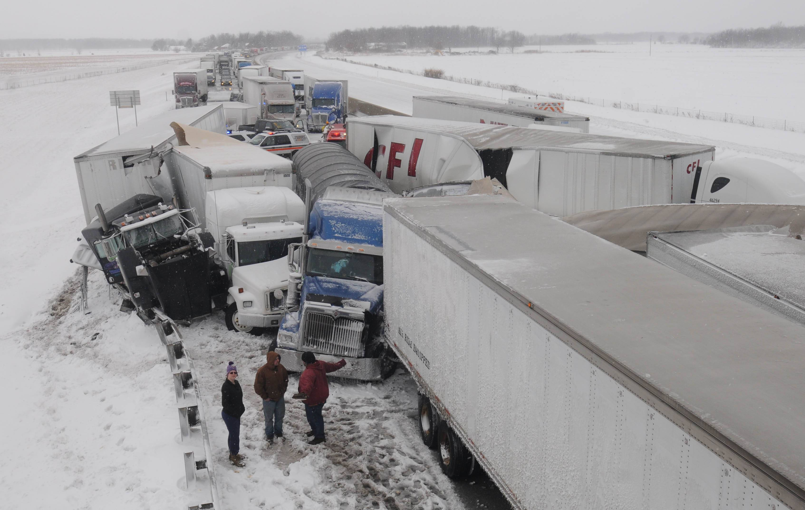 Truck drivers talk at the scene of an accident on the Ohio Turnpike, northeast of Clyde, Ohio, after more than 50 vehicles crashed, Wednesday.