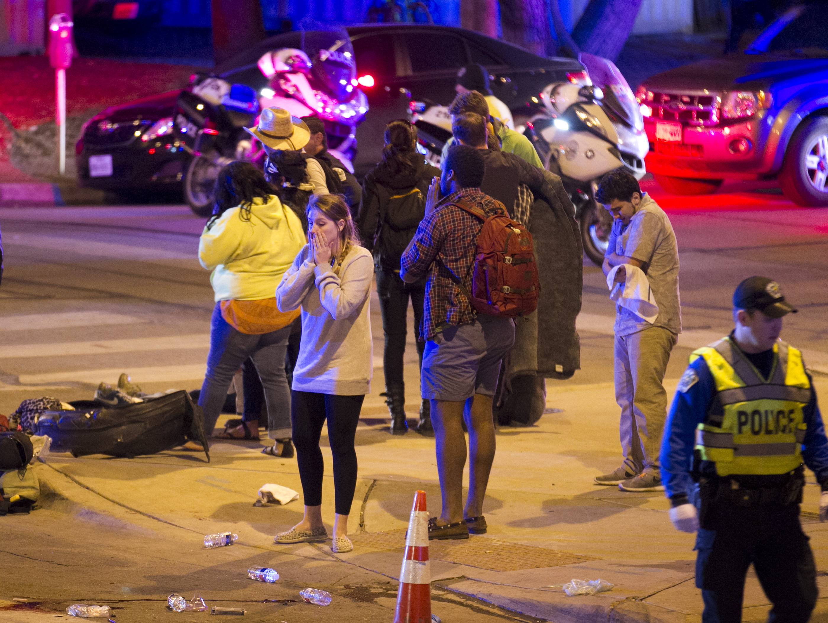 Bystanders react after several people were struck by a vehicle on Red River Street in downtown Austin, Texas, at SXSW on Wednesday March 12, 2014. Police say two people were confirmed dead at the scene after a car drove through temporary barricades set up for the South By Southwest festival and struck a crowd of pedestrians.
