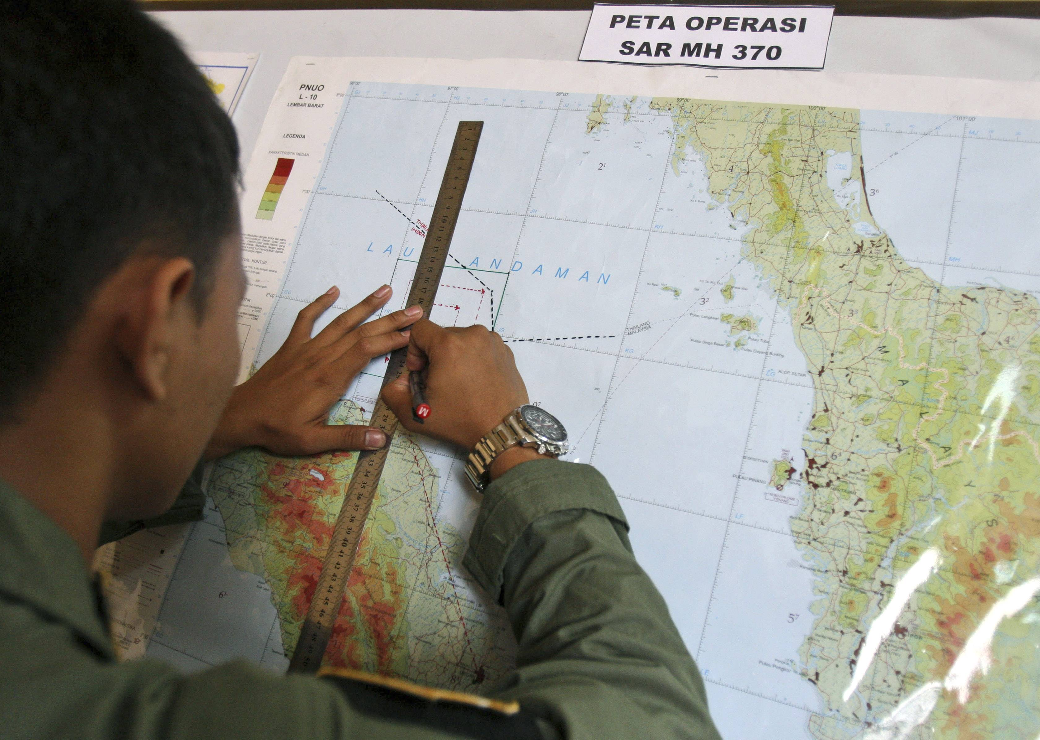 An Indonesian Air Force officer draws a flight pattern flown earlier in a search operation for the missing Malaysia Airlines Boeing 777, during a post-mission briefing in Indonesia on Thursday.
