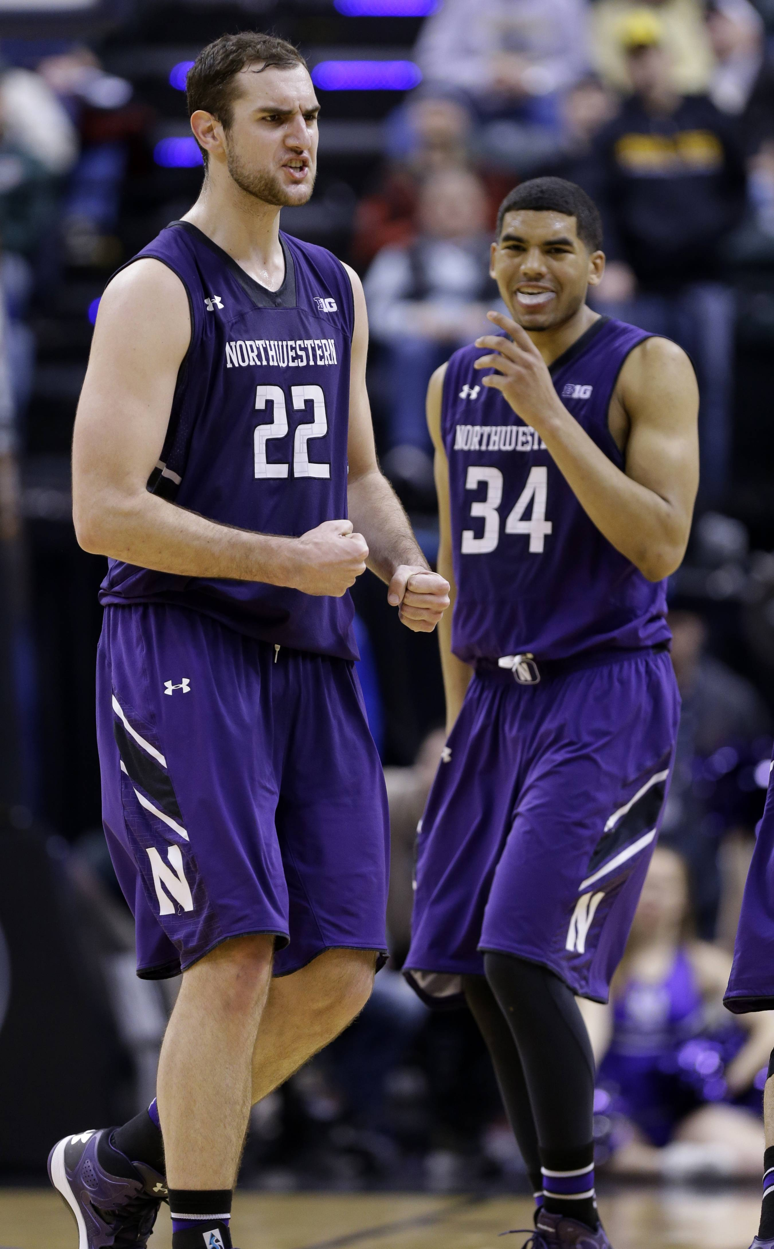 Northwestern center Alex Olah (22) pumps his fists after making free throws in the second half of an NCAA college basketball game against Iowa in the first round of the Big Ten Conference tournament, Thursday, March 13, 2014, in Indianapolis. At right is Northwestern guard/forward Sanjay Lumpkin. Northwestern won 67-62. (AP Photo/Michael Conroy)
