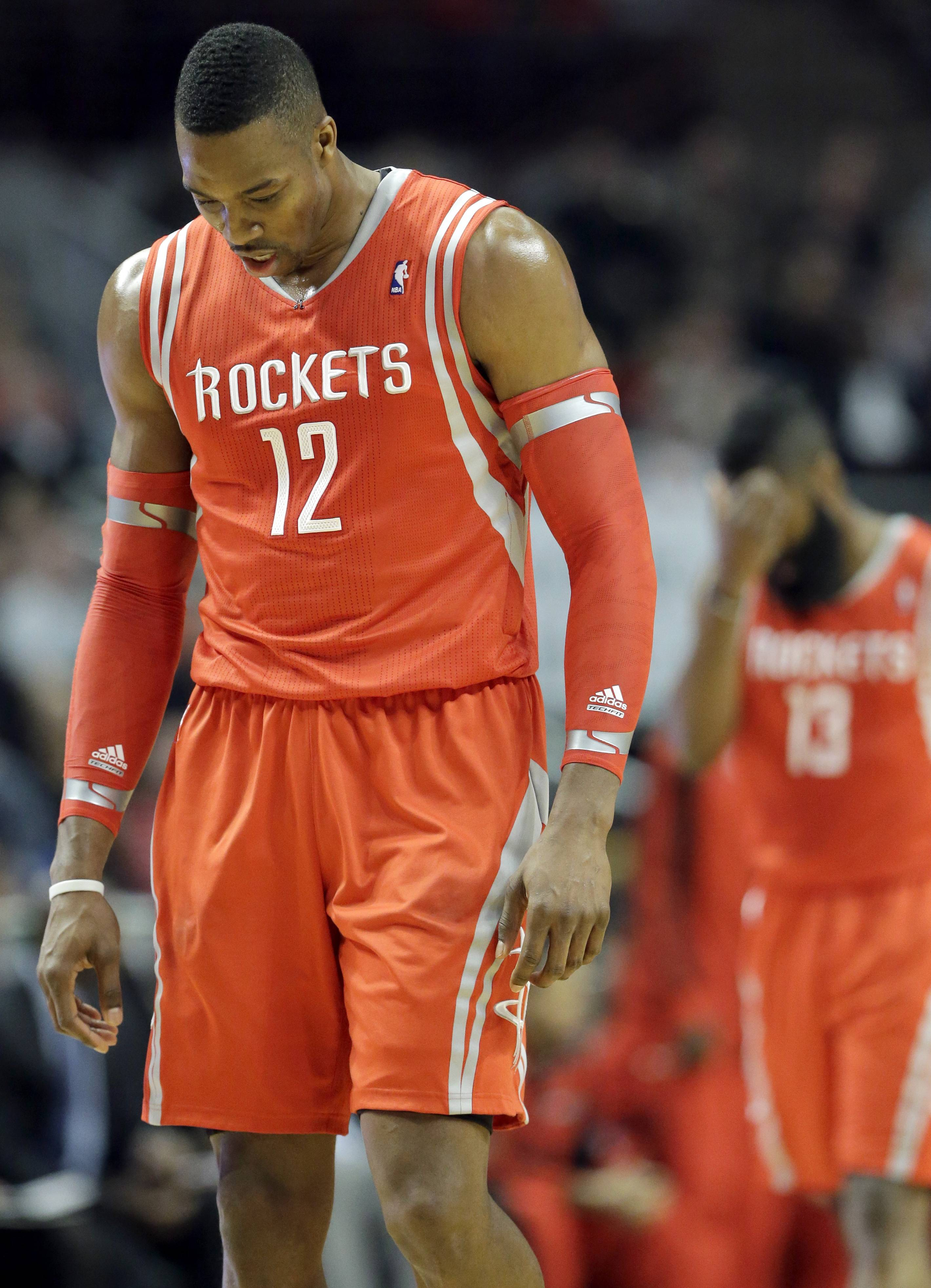 Houston Rockets forward Dwight Howard (12) and James Harden (13) walk back to the bench during the second half of an NBA basketball game against the Chicago Bulls in Chicago, Thursday, March 13, 2014. The Bulls won 111-87. (AP Photo/Nam Y. Huh)