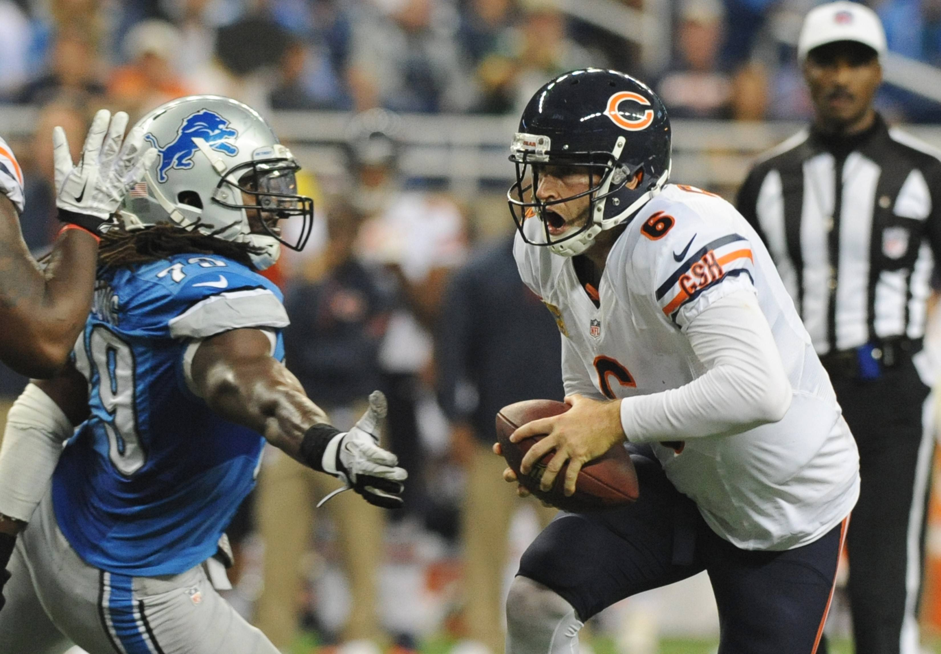 Chicago Bears quarterback Jay Cutler scrambles while chased by Detroit Lions defensive end Willie Young last September. Young signed a three-year deal worth $9 million to play for the Bears.