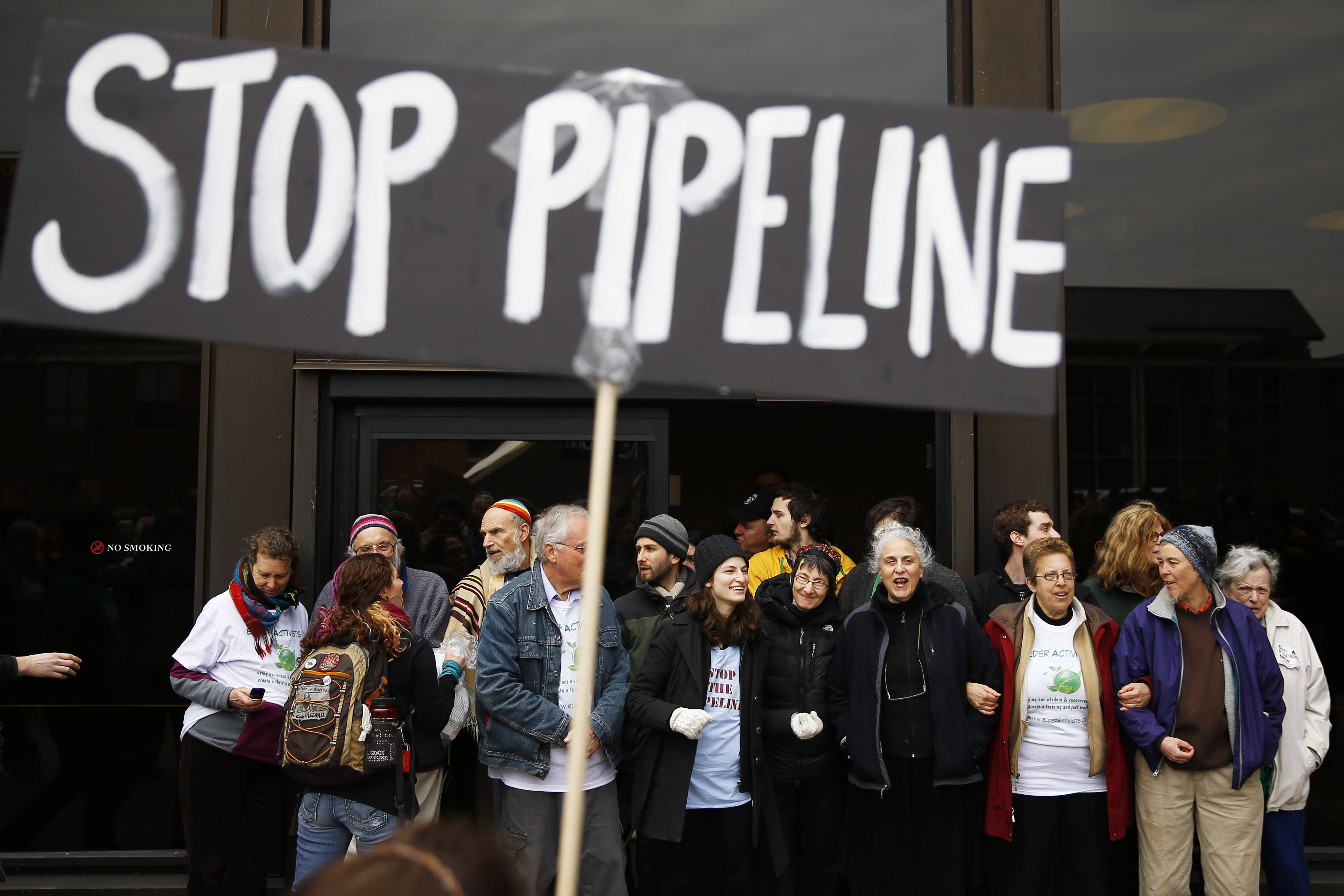 Protesters demonstrating in opposition to the proposed Keystone XL oil pipeline Monday block the door to the federal building in Philadelphia. The protestors said the pipeline would contribute to global warming.